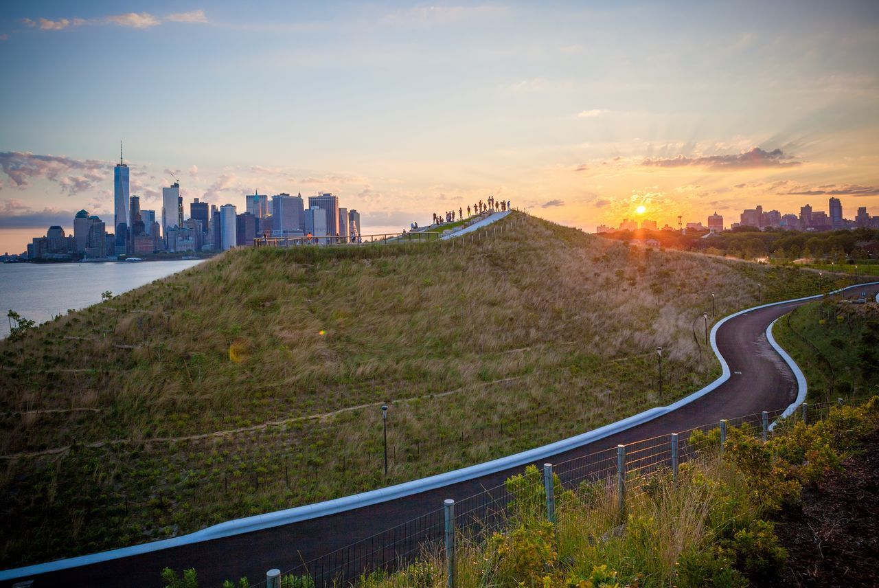The sun rises over Brooklyn and bathes Manhattan in early morning light as a crowd of early-risers greet the morning from the top of The Hills at Governors Island New York City New York Brooklyn Green Manhattan Manhattan Skyline Governors Island The Hills Silhouette People Morning Morning Sky Sunrise Sun Outdoors