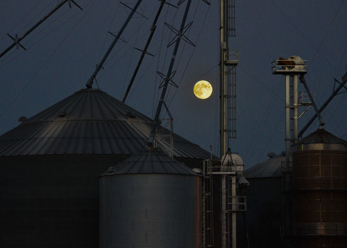 Harvest Moon Over Iowa Agriculture EyeEmNewHere Farm Full Moon Harvest Moon Iowa Moon Silhouette Twilight Built Structure Corn Crops Ethanol Farming Grain Harvest Metal Structure Moonrise Night Silo