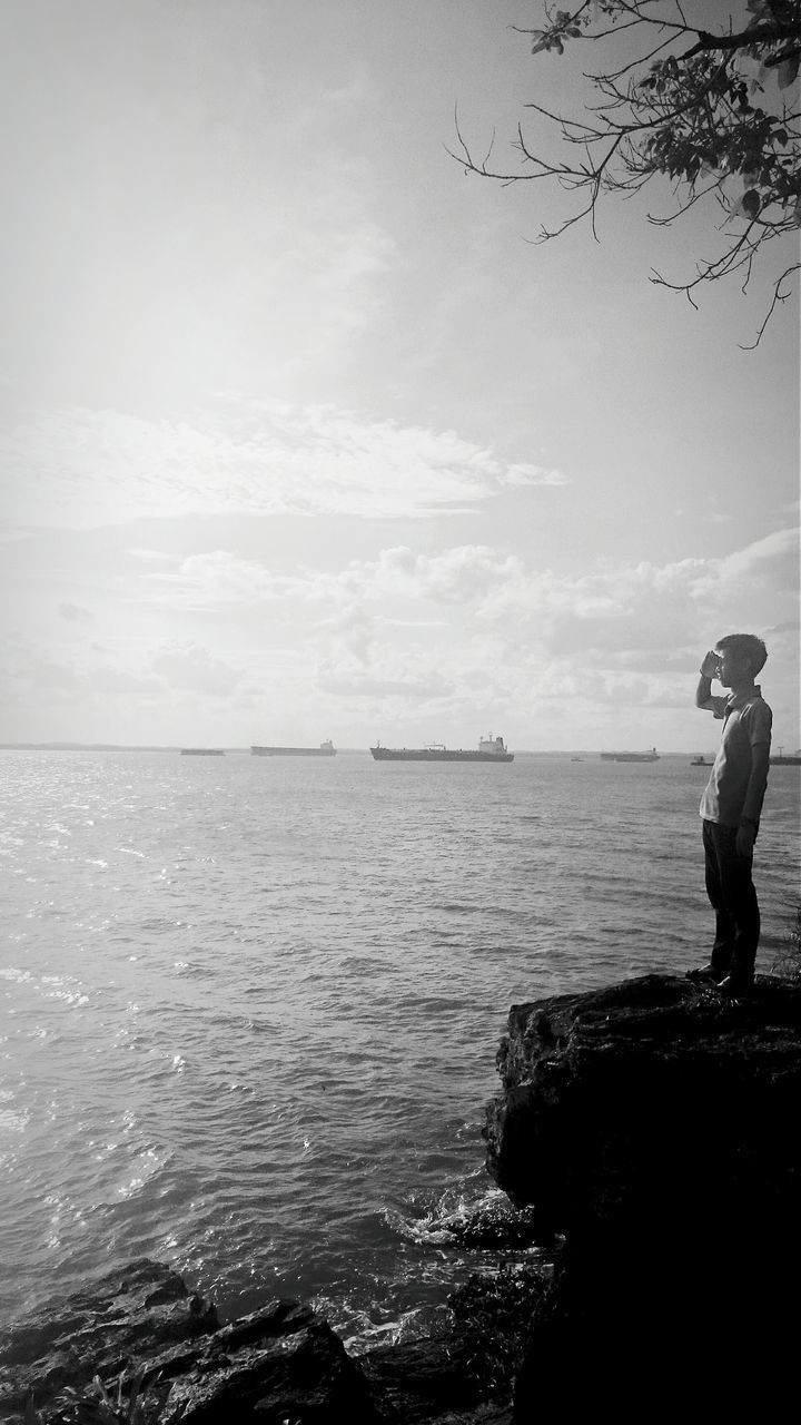sea, water, standing, real people, horizon over water, nature, full length, one person, sky, tranquil scene, beauty in nature, scenics, rock - object, side view, cloud - sky, outdoors, tranquility, leisure activity, silhouette, women, day, men, lifestyles, fishing pole, people