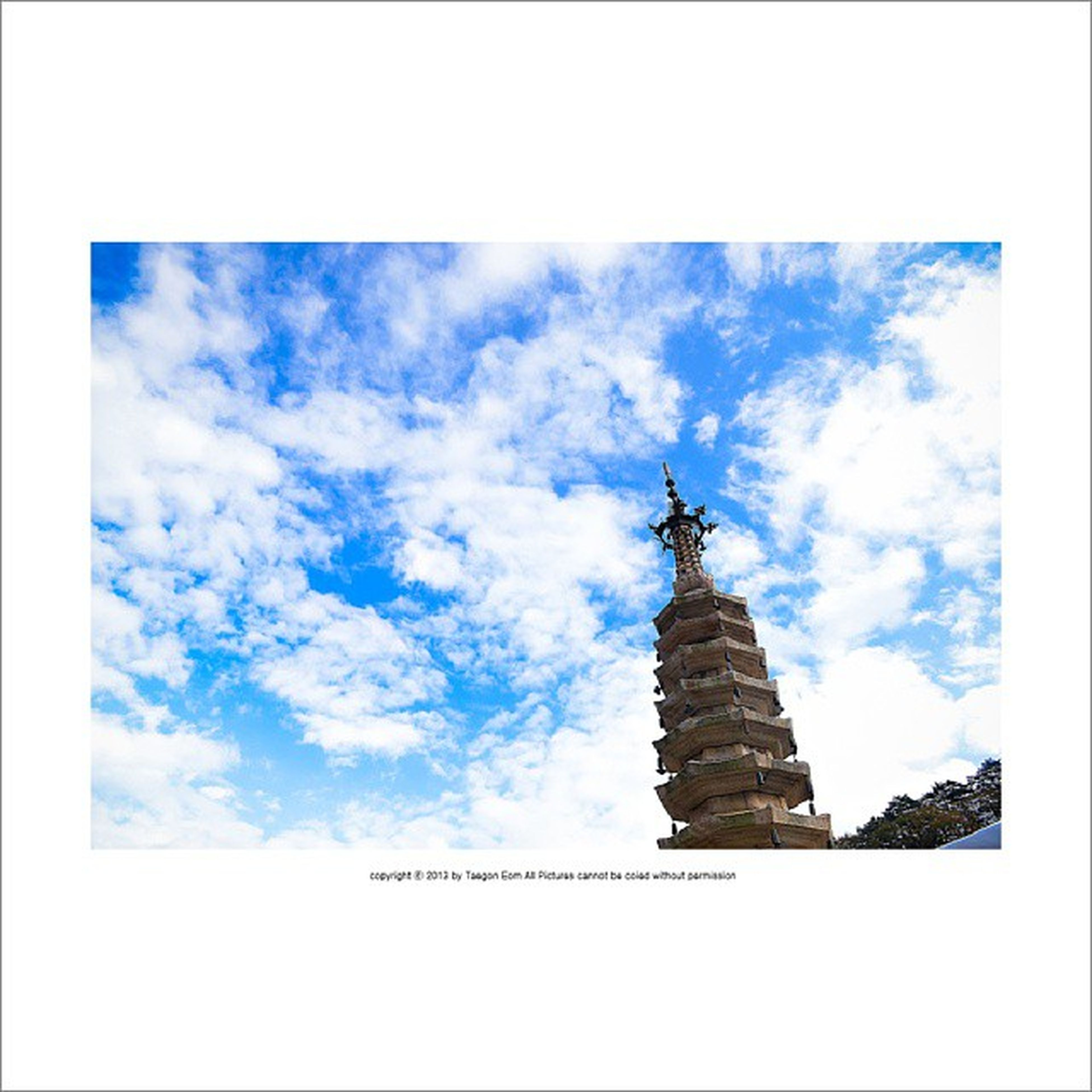 transfer print, sky, low angle view, auto post production filter, cloud - sky, cloud, cloudy, outdoors, day, built structure, nature, high section, no people, silhouette, overcast, tranquility, architecture, copy space, vignette, blue