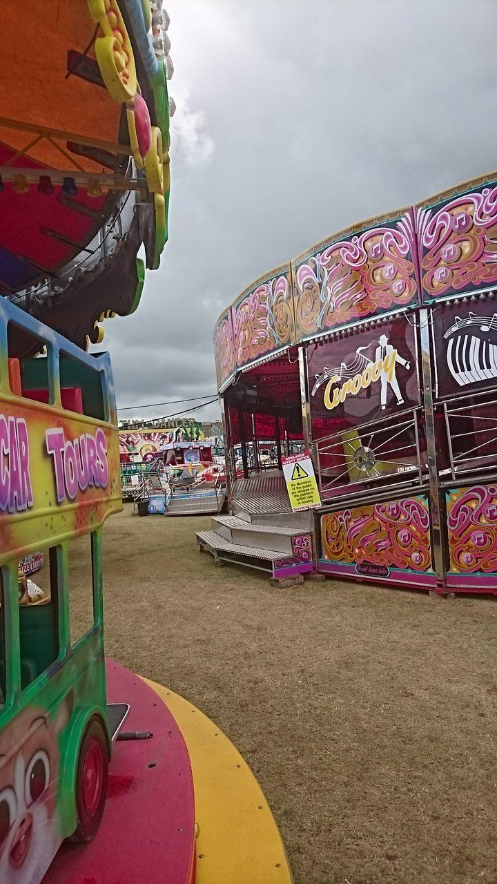 amusement park, multi colored, sky, cloud - sky, arts culture and entertainment, text, outdoors, amusement park ride, carousel, day, leisure activity, no people