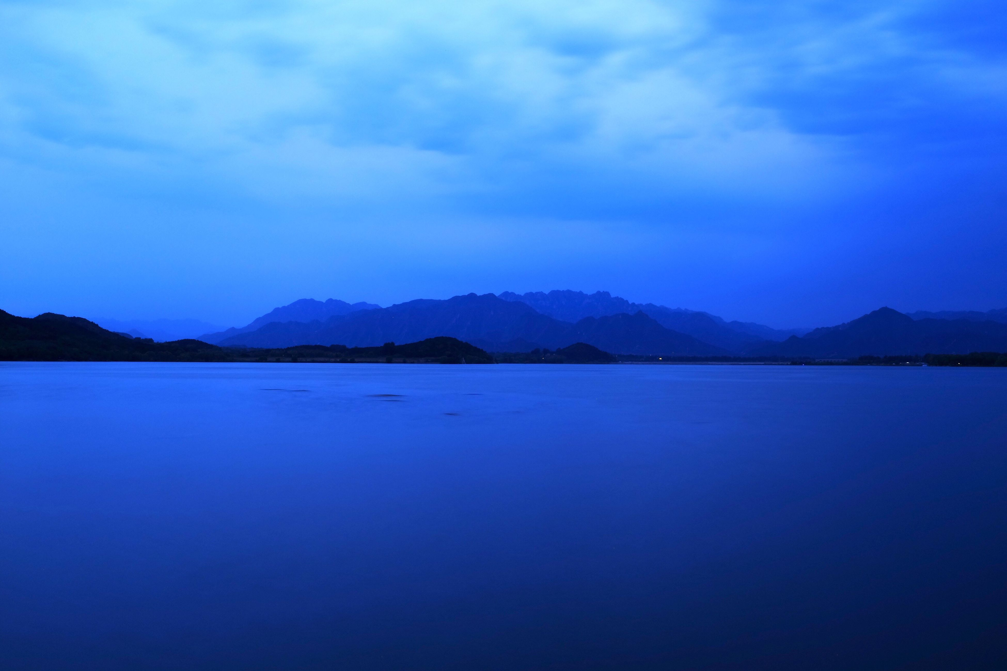 tranquil scene, water, scenics, tranquility, mountain, beauty in nature, sky, mountain range, blue, nature, lake, cloud - sky, waterfront, idyllic, reflection, sea, cloud, calm, dusk, outdoors