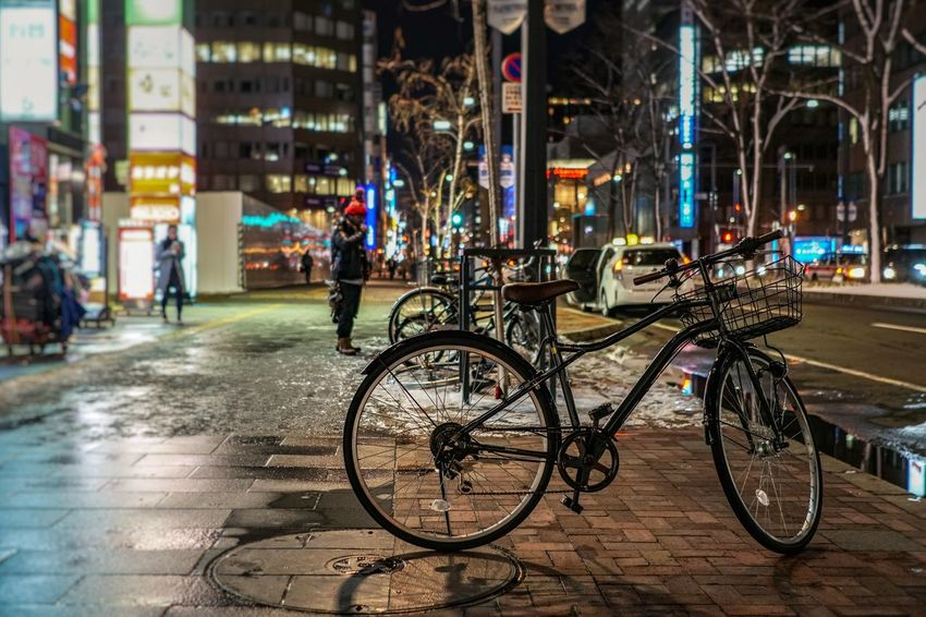 A famous mode of transportation in Japan - the classic bicycle. Japan Hokkaido Hokkaido Japan Outdoors Snow Spring Travel Destinations Transportation Nightphotography Night City Bicycle Street Illuminated Architecture Building Exterior Cliche
