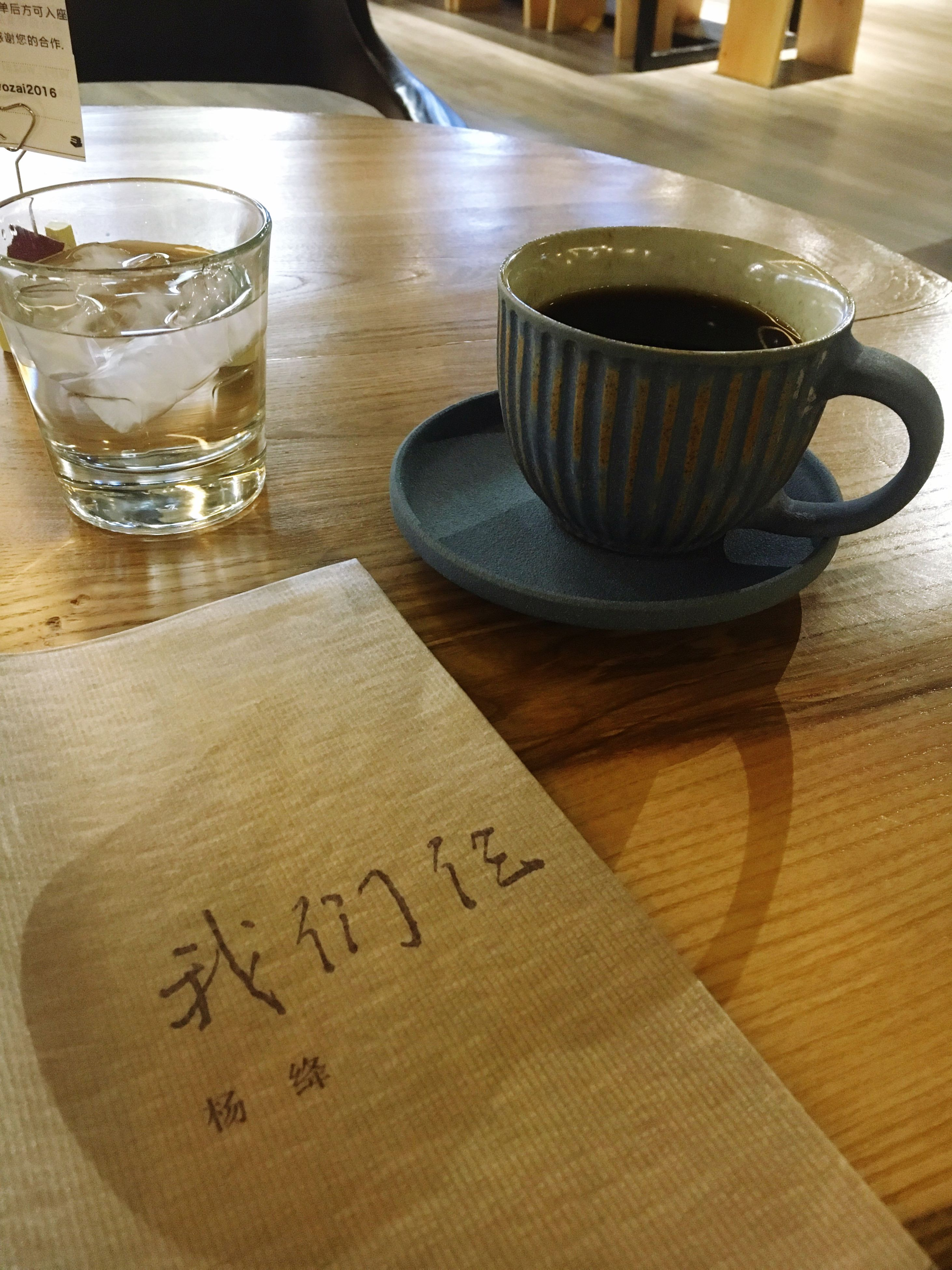 indoors, table, drink, food and drink, refreshment, still life, freshness, coffee cup, drinking glass, coffee - drink, close-up, text, western script, saucer, wood - material, no people, high angle view, cup, coffee, restaurant