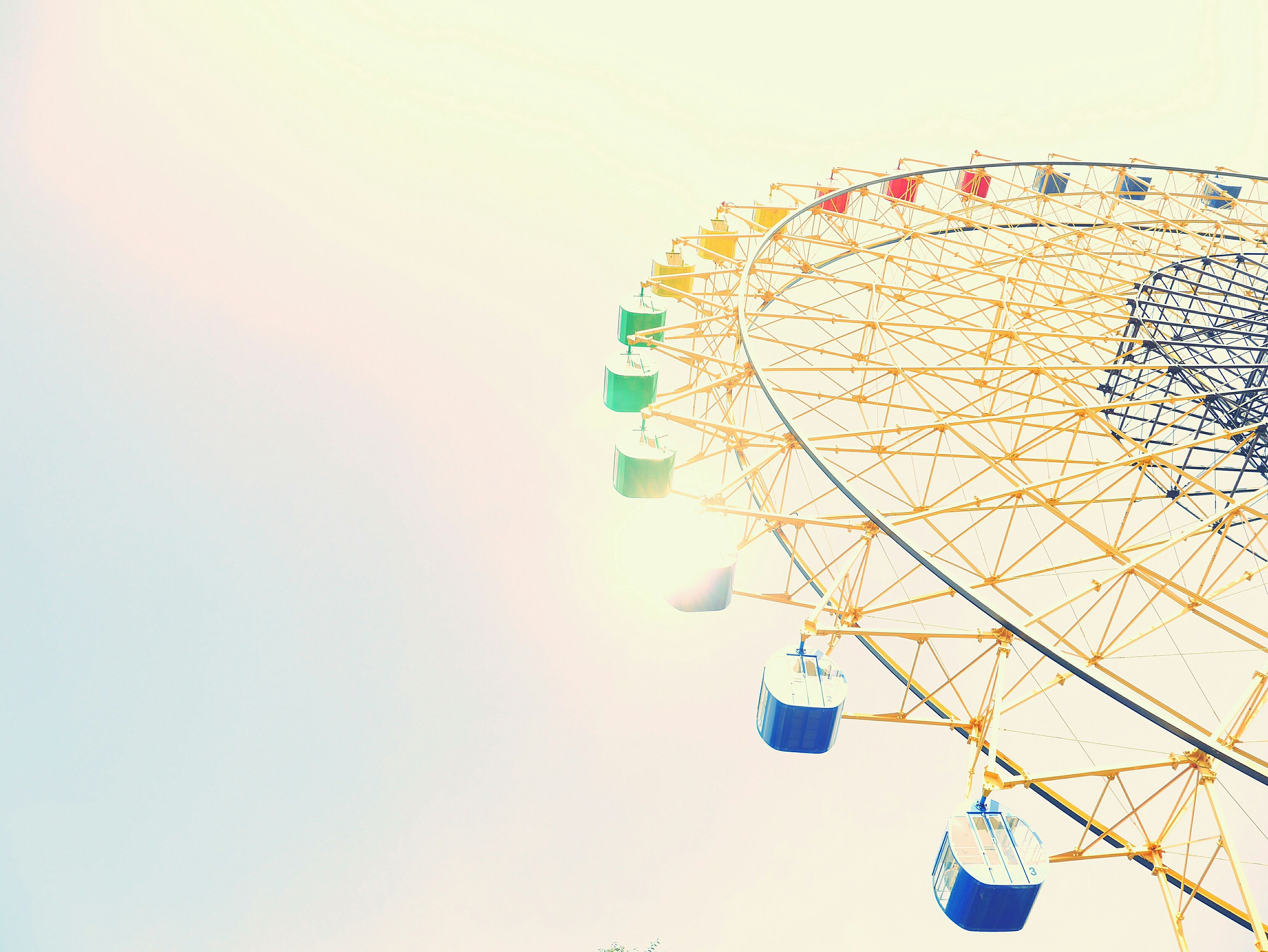 low angle view, amusement park, ferris wheel, clear sky, amusement park ride, built structure, arts culture and entertainment, architecture, building exterior, copy space, sky, circle, outdoors, tall - high, day, multi colored, no people, pattern, modern, tree
