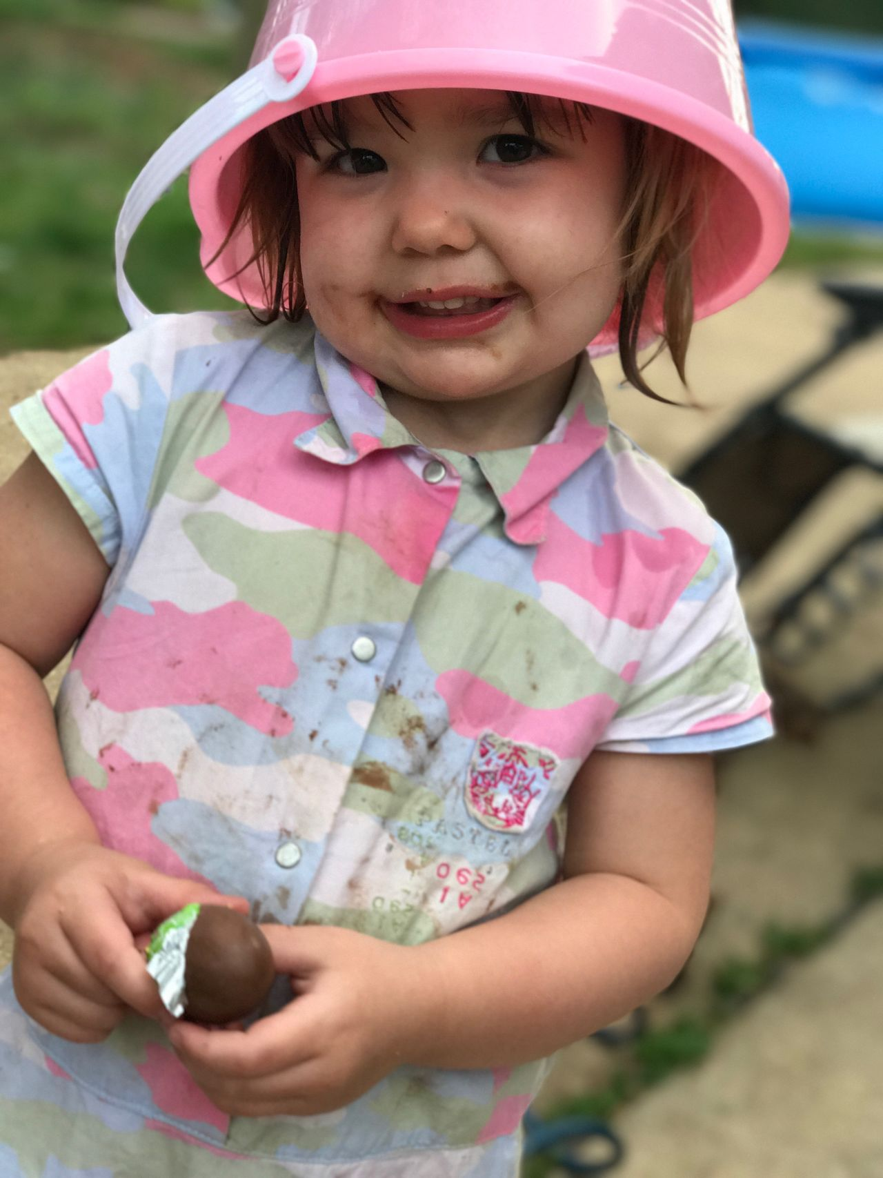 Toddler enjoying her candy with pink pail on head Outdoors Cute Smiling Close-up Happiness Low Angle View The Portraitist - 2017 EyeEm Awards