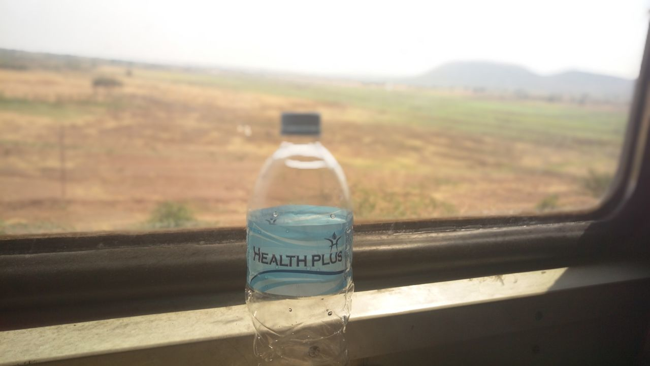 bottle, text, day, no people, focus on foreground, landscape, communication, sunlight, close-up, nature, outdoors, sky