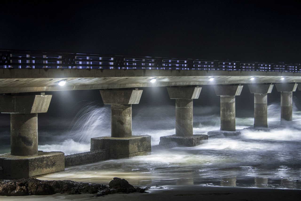Pier-ing out into the dark ocean. Architectural Column Architecture Bridge - Man Made Structure Built Structure City Concrete Connection Engineering Illuminated Jetty Night Night Lights Nightphotography Nightshot Ocean Outdoors Pier Rough Rough Sea Sea Sky Water Waves