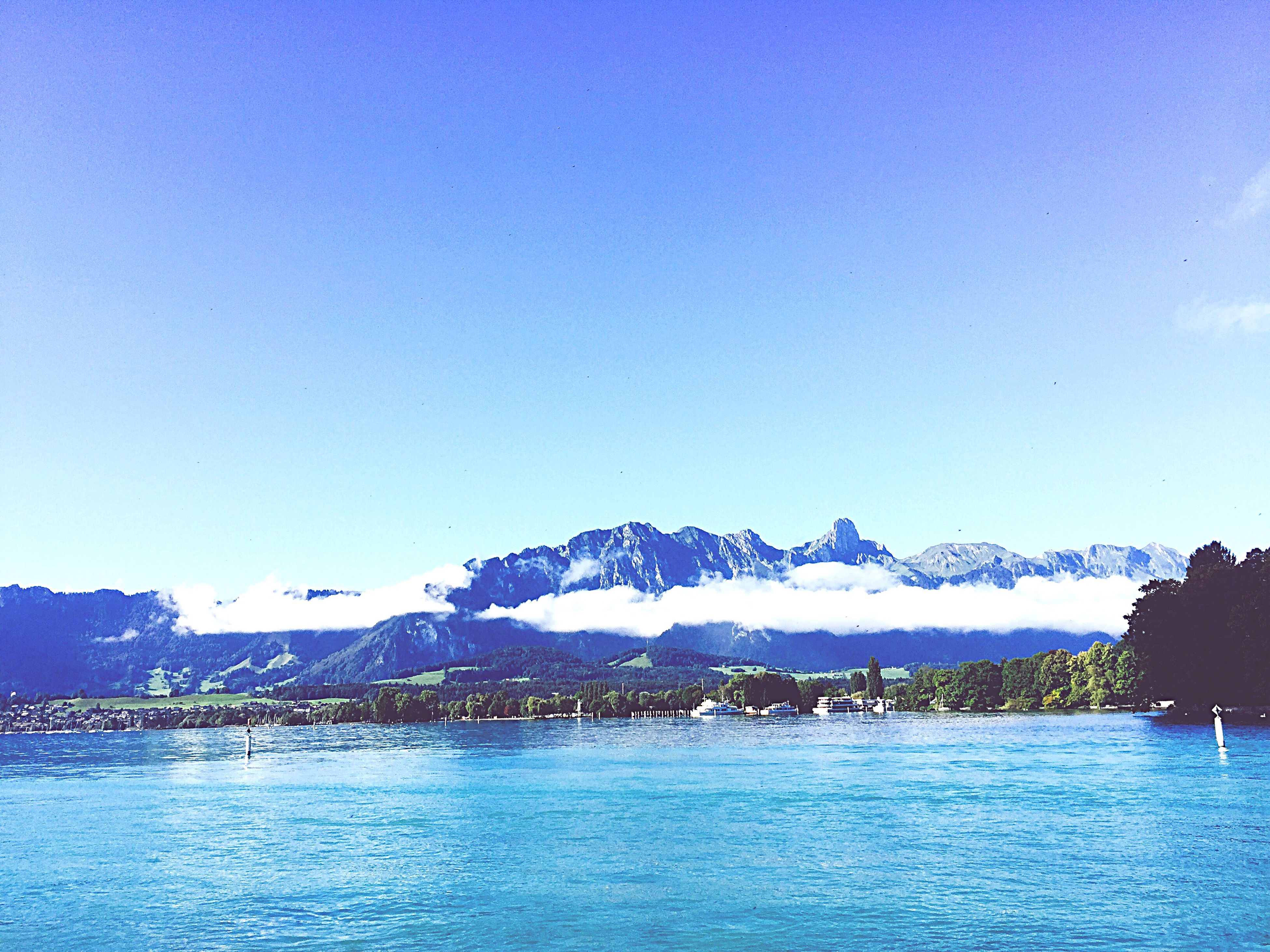 clear sky, mountain, blue, tranquil scene, water, copy space, scenics, tranquility, waterfront, mountain range, beauty in nature, nature, day, non-urban scene, calm, outdoors, sea, water surface, no people, majestic, solitude, remote, dreamlike, vibrant color, vacations