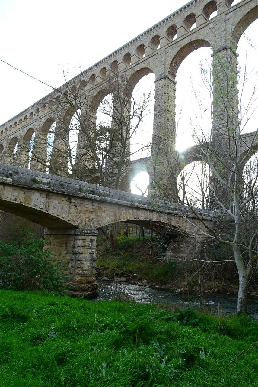 arch, bridge - man made structure, connection, architecture, viaduct, built structure, low angle view, day, transportation, old ruin, outdoors, green color, grass, history, nature, no people, growth, travel destinations, sky