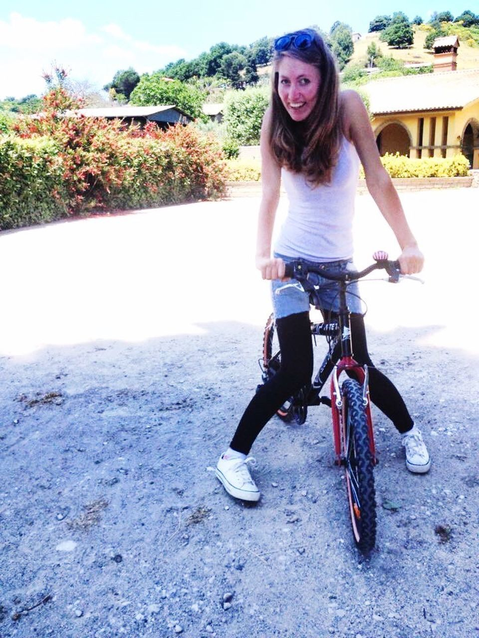 bicycle, looking at camera, front view, real people, smiling, portrait, day, outdoors, leisure activity, happiness, full length, one person, transportation, lifestyles, road, young adult, young women, sky