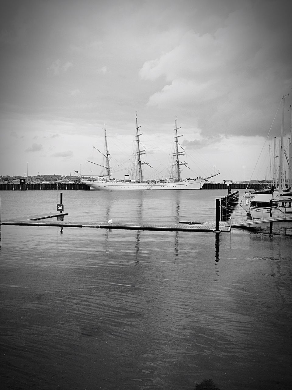 Ship Moored At Harbor Against Cloudy Sky