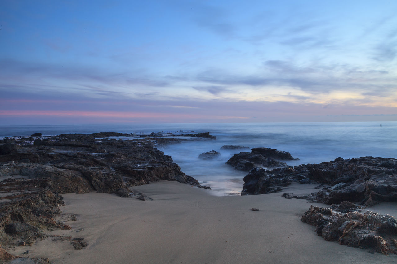 Sunset over the rocks at Shaws Cove in Laguna Beach as water flows over the stone Beach Beach Photography Beauty In Nature Coastline Horizon Over Water Horizontal Laguna Beach No People Ocean Outdoors Sand Scenics Sea Shaws Cove Sky Southern California Sunset