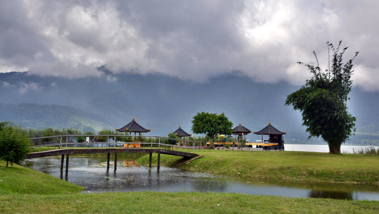 View Of Gazebos Next To River Against Cloudy Sky
