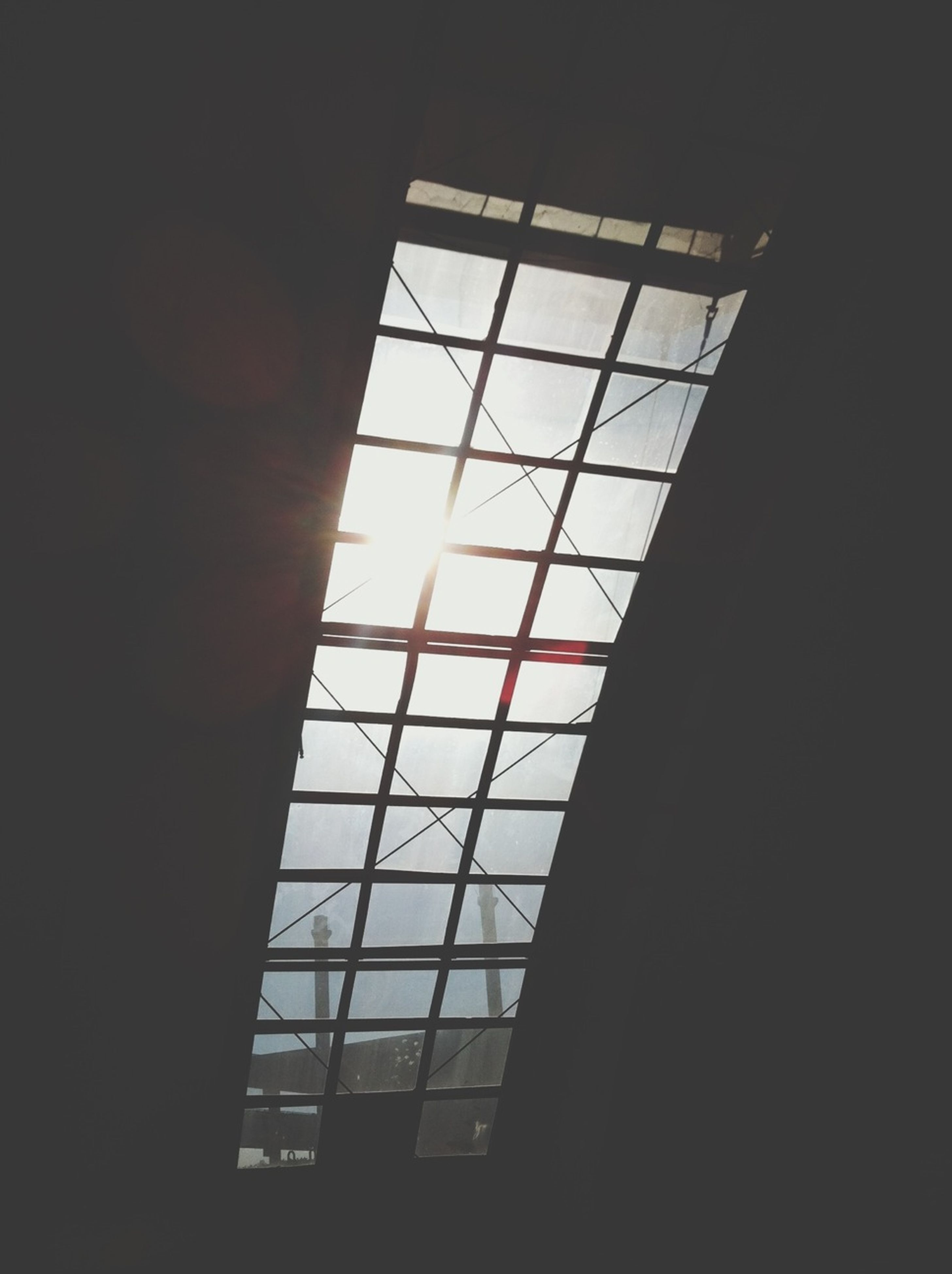 indoors, window, glass - material, architecture, built structure, transparent, low angle view, geometric shape, glass, silhouette, building, ceiling, sky, sunlight, skylight, modern, reflection, no people, pattern, building exterior