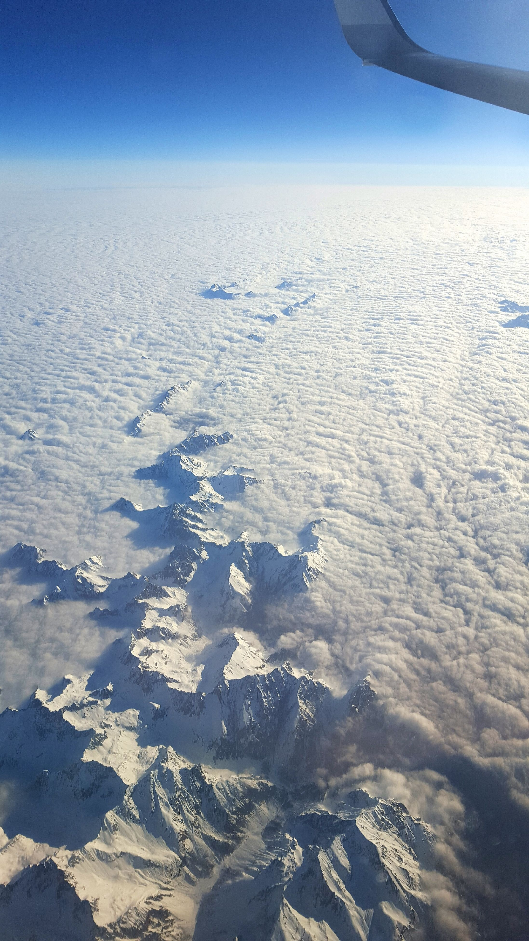 water, scenics, aerial view, tranquil scene, beauty in nature, tranquility, transportation, nature, flying, blue, landscape, part of, sea, sky, mode of transport, snow, winter, cropped, aircraft wing, travel