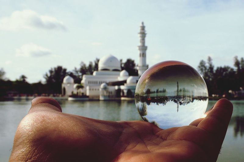 A Beautiful View Of Masjid Tengku Tengah Zaharah Or Locally Known As Floating Mosque in Crystal Ball. Crystal Crystal Clear Crystal Ball Mininalist Architecture Minimalist Landmark Mosque Reflection Ball Cristal Lake Floating Mosque Floating On Water Building Exterior Muslim Islamic Architecture Pray Dome White Human Hand Human Body Part Water Sky Architecture One Person People Built Structure Adult Day Close-up Outdoors EyeEmNewHere An Eye For Travel
