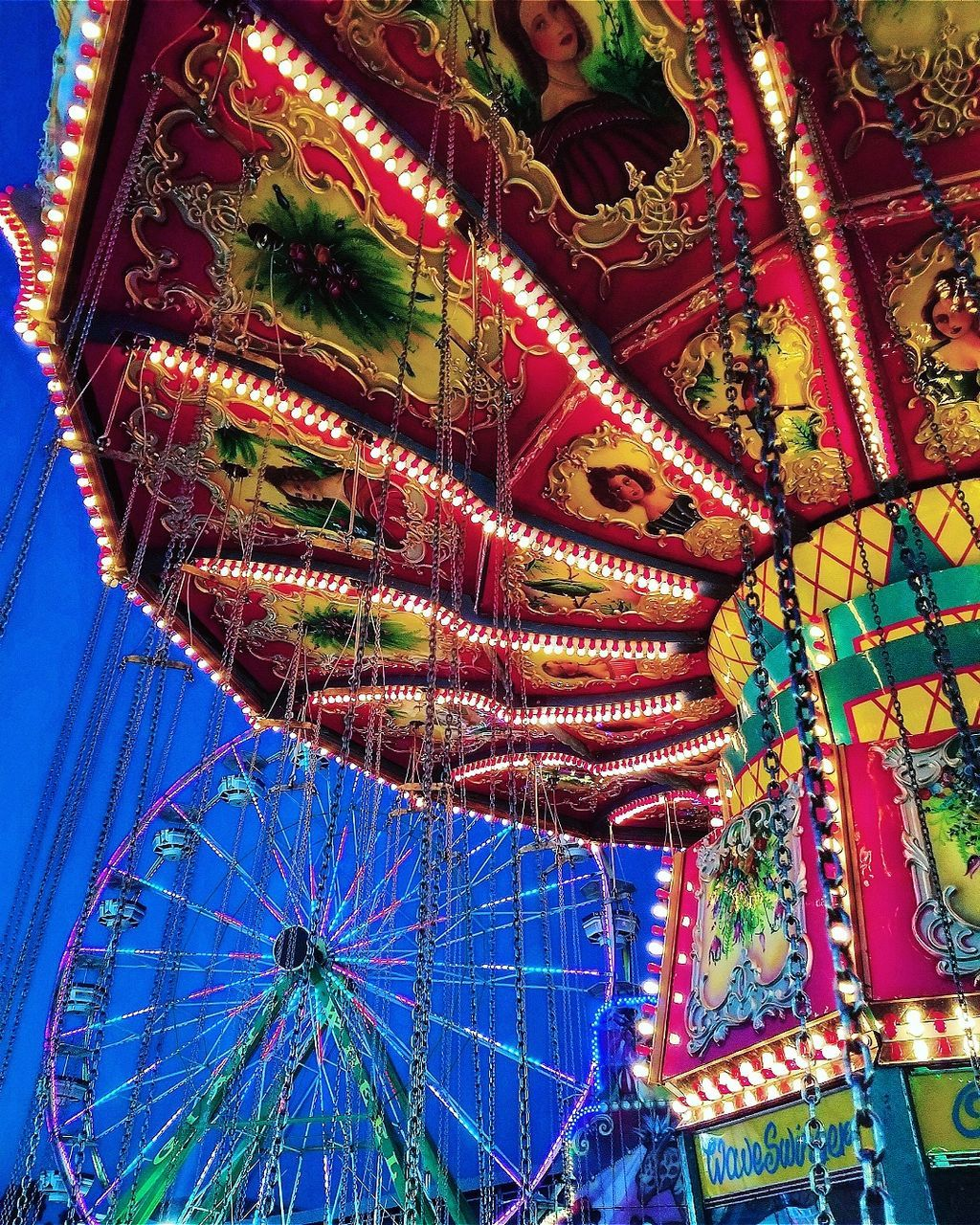 amusement park, arts culture and entertainment, amusement park ride, ferris wheel, carousel, low angle view, leisure activity, fun, blue, multi colored, outdoors, no people, day, merry-go-round, clear sky, illuminated, close-up, sky