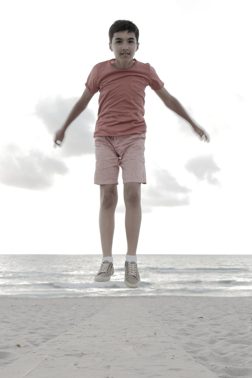Portrait Of Boy Jumping At Beach Against Sky