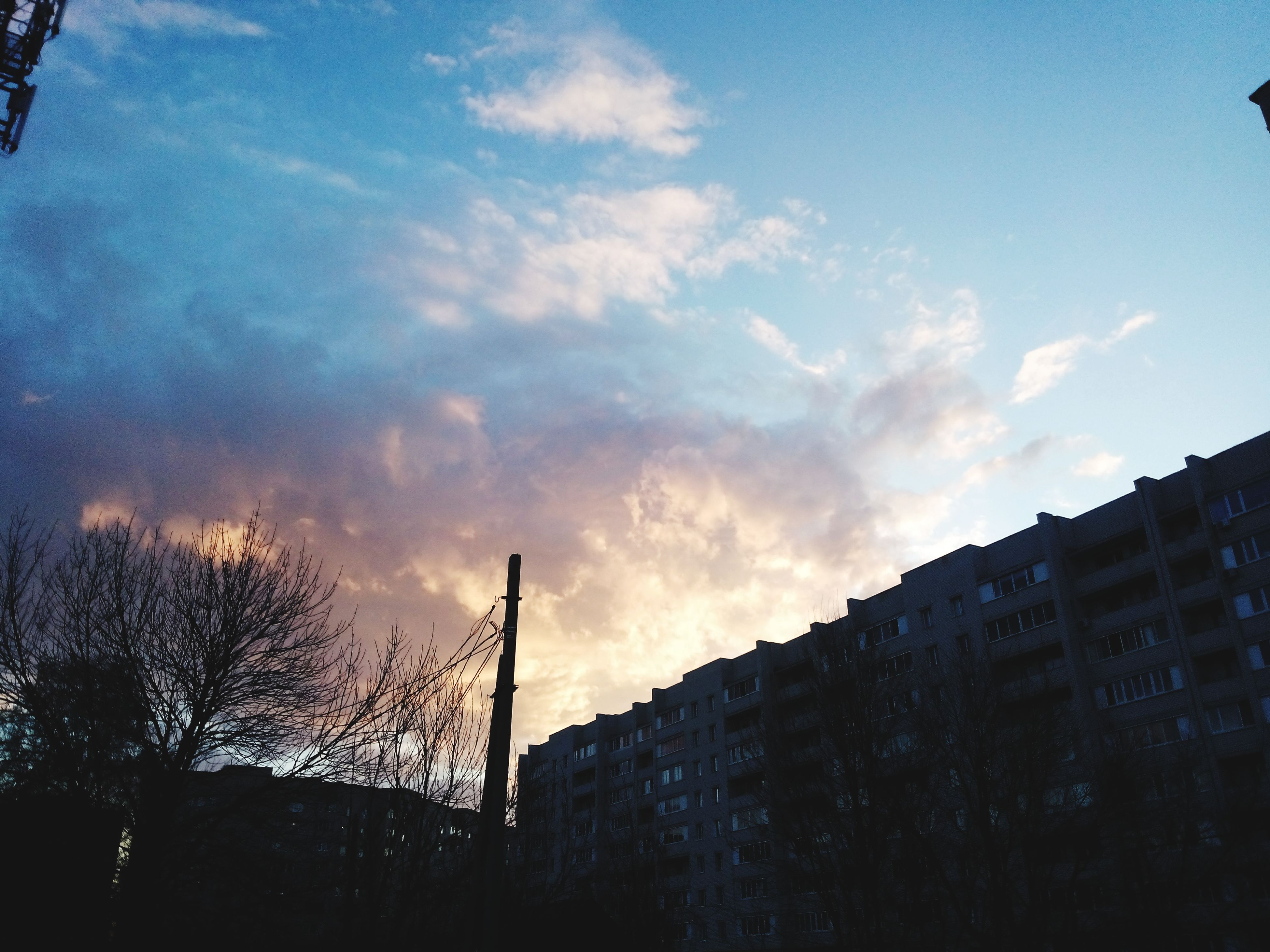 building exterior, architecture, built structure, low angle view, sky, cloud - sky, city, silhouette, building, tower, cloud, tree, tall - high, cloudy, sunset, outdoors, dusk, no people, skyscraper, residential building