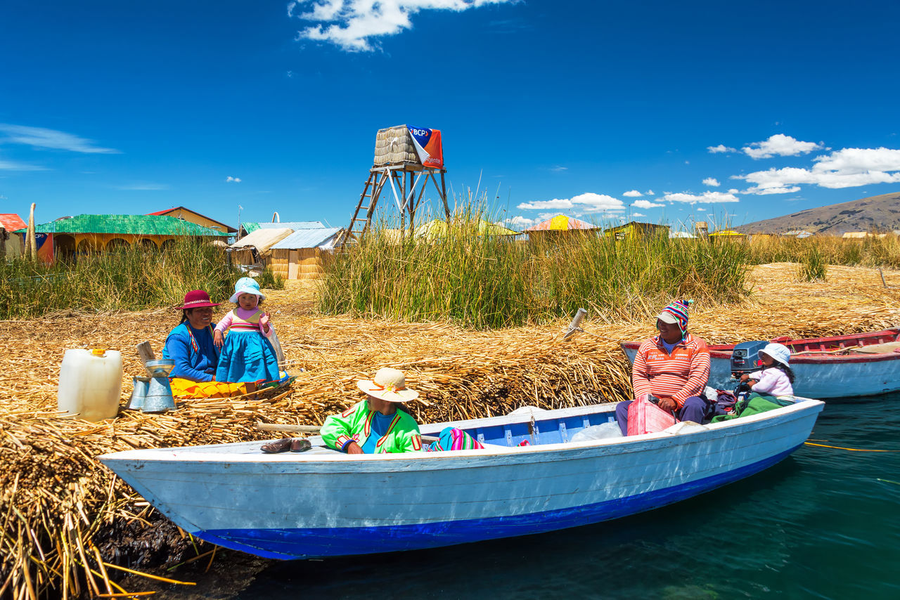 PUNO, PERU - SEPTEMBER 19: Locals conversing on the Uros Floating Islands near Puno, Peru on September 19, 2014 Aymara Floating Indigenous  Island Islands Lake Titicaca Man Made Object Manmade People Peru Puno Reed Reeds Totora Tourism Travel Travel Destinations Uros Uros Island Uros Island - Lake Titicaca Uros Islands Uros Islands - Titicaca Lake Women