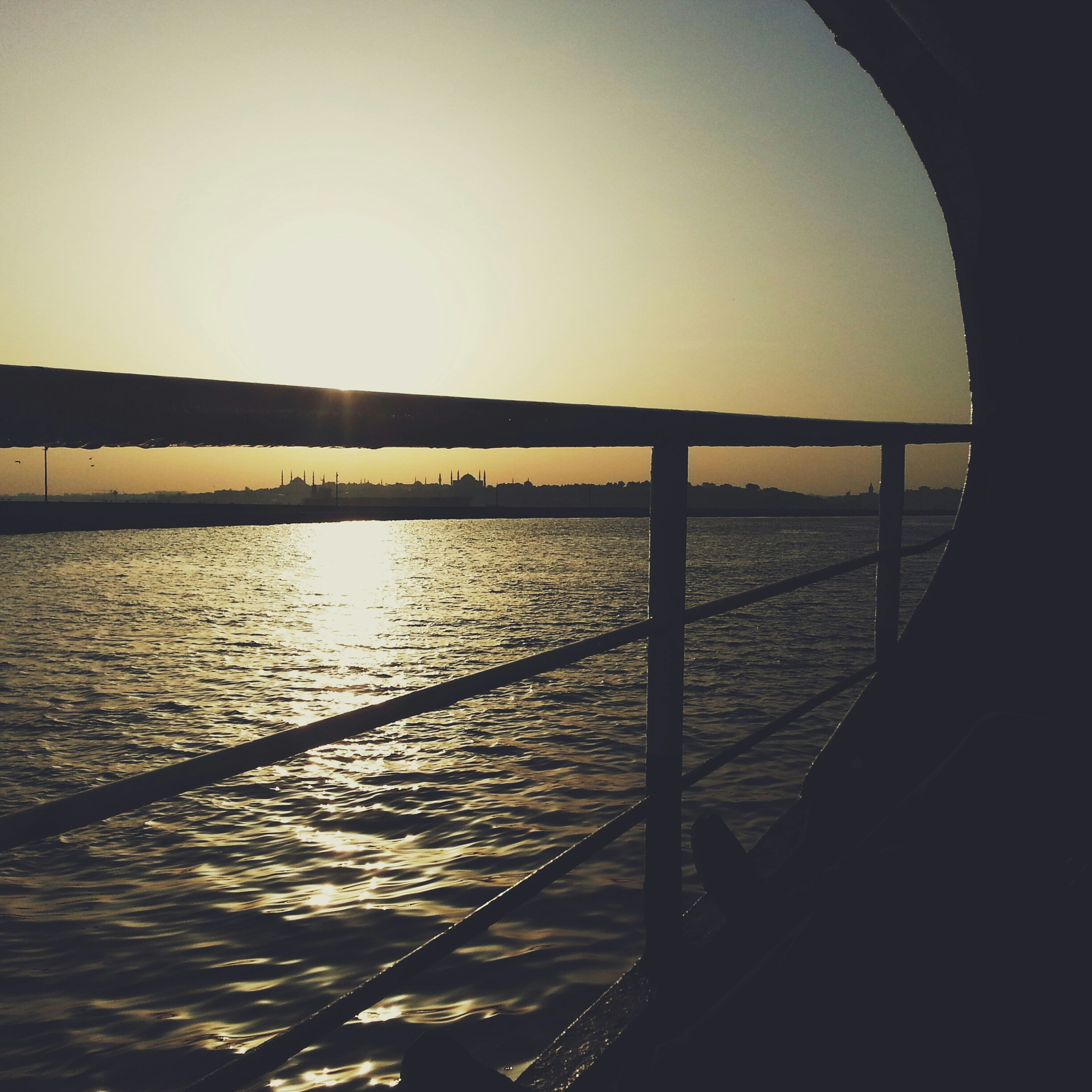 water, sunset, clear sky, sea, sun, transportation, silhouette, tranquil scene, tranquility, scenics, reflection, copy space, beauty in nature, river, sunlight, nature, nautical vessel, railing, sky, boat
