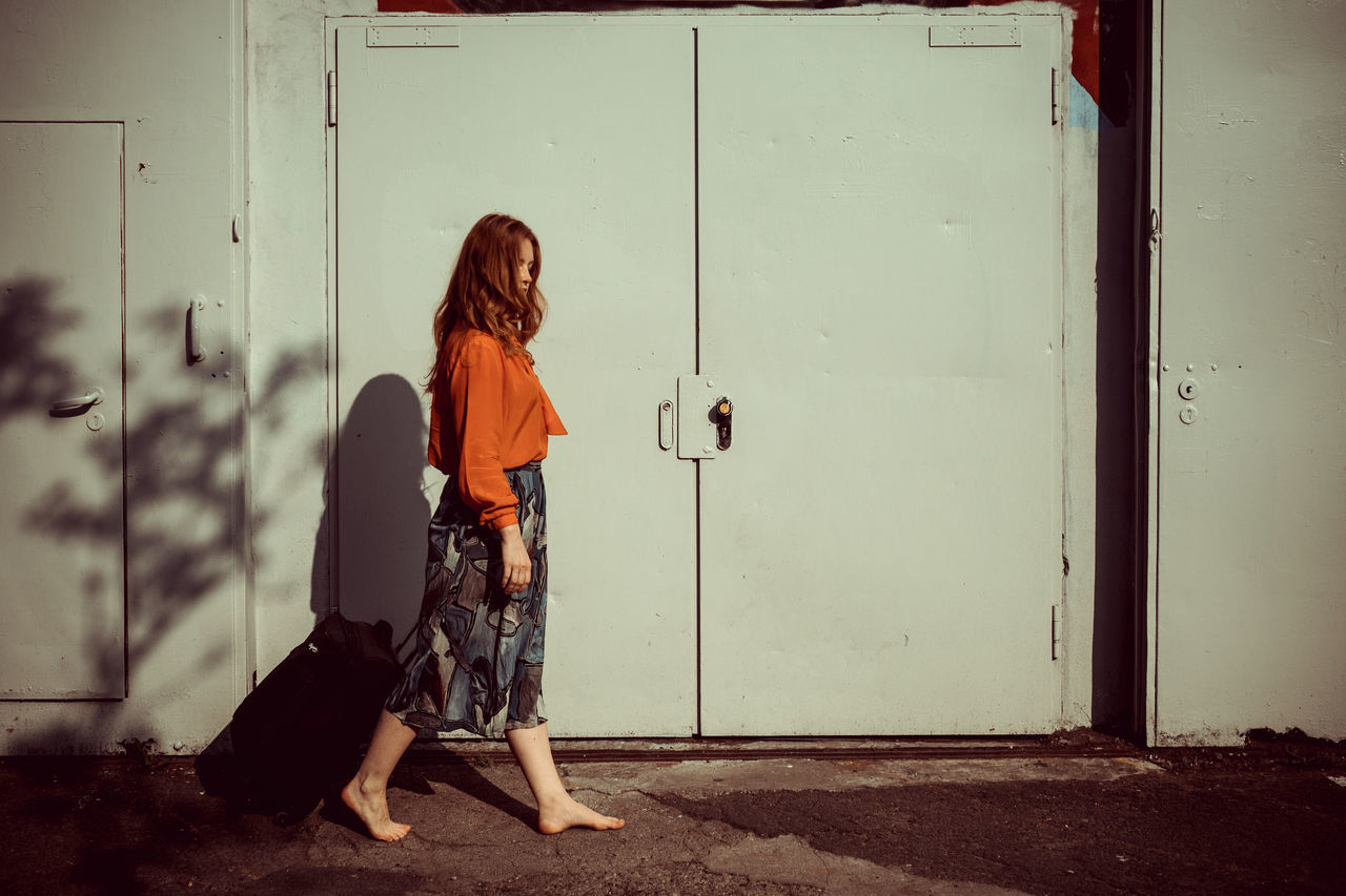 Young woman walking with a trolley from left to right Barefeet No Shoes Outdoor Portrait Travel Traveling Vacation Walking Walking Woman Woman