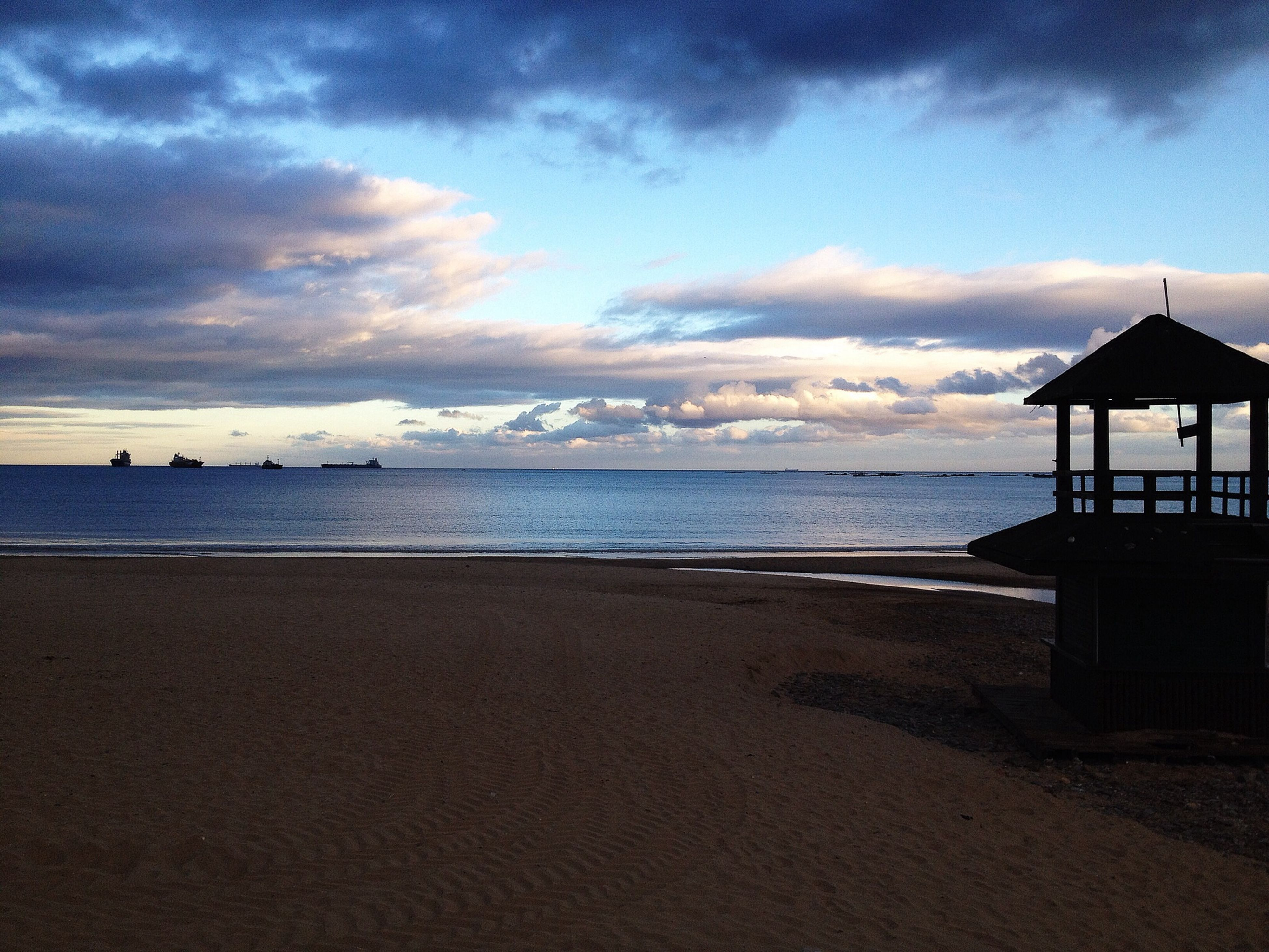 sea, horizon over water, beach, sky, water, shore, sand, tranquil scene, scenics, tranquility, cloud - sky, beauty in nature, built structure, cloud, nature, architecture, idyllic, building exterior, cloudy, calm