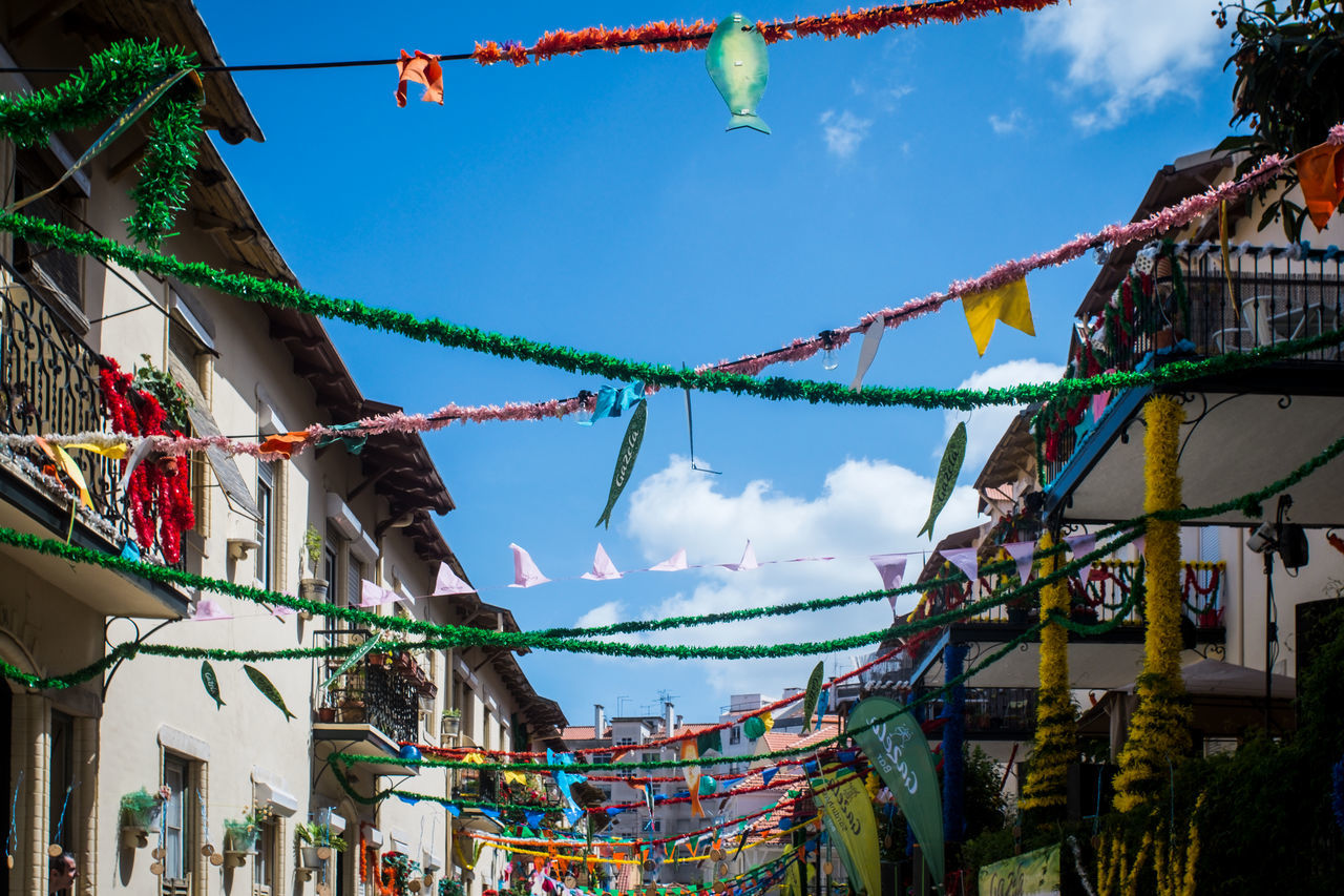 hanging, bunting, multi colored, building exterior, built structure, low angle view, architecture, sky, day, outdoors, celebration, tradition, cultures, religion, clothesline, cloud - sky, flag, no people, streamer
