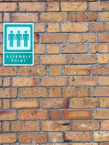 Assembly point Assembly Point Sign Assembly Point Sign Text Brick Wall Western Script Communication Guidance