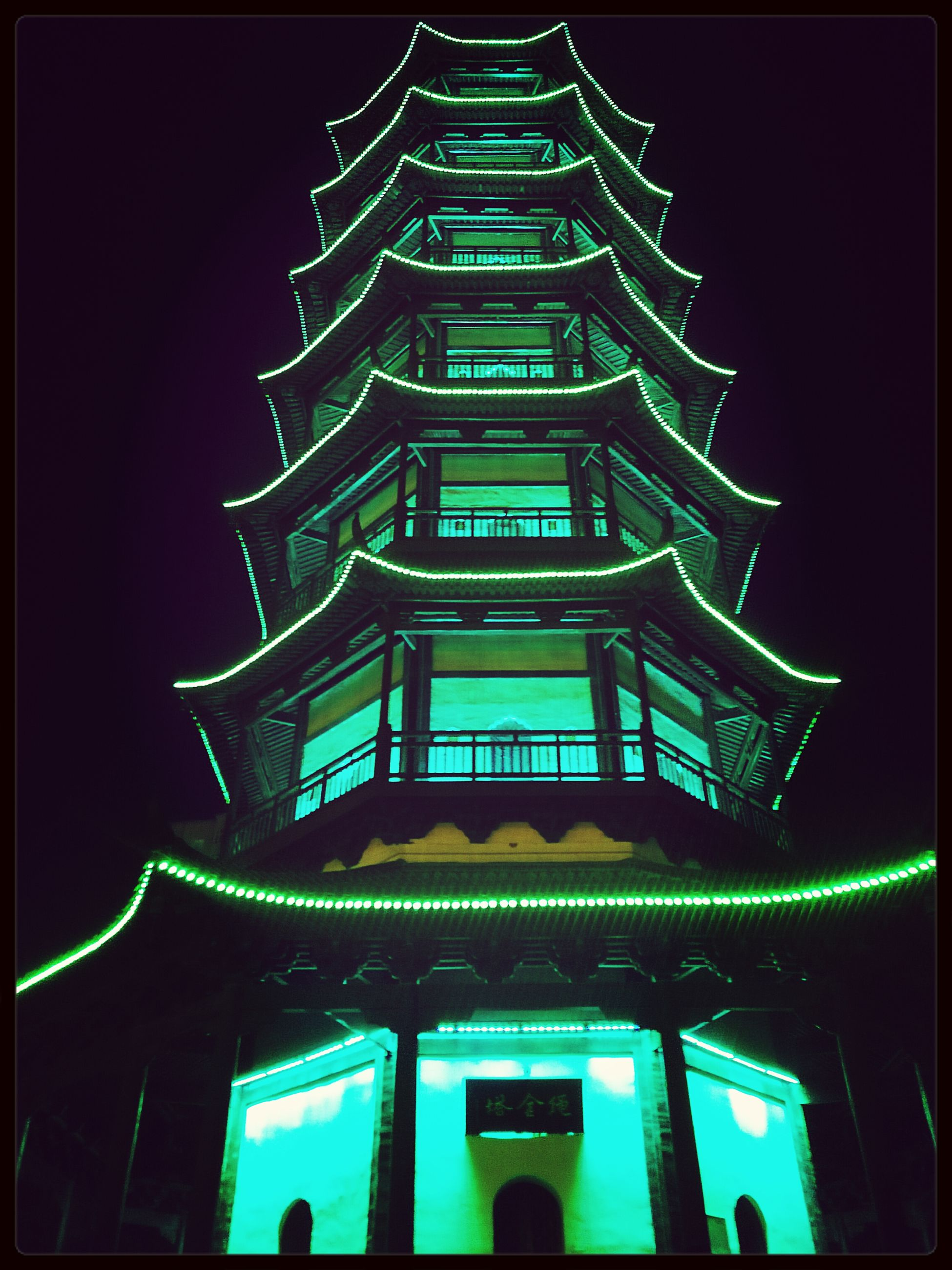 low angle view, architecture, built structure, building exterior, illuminated, night, religion, place of worship, sky, spirituality, famous place, pattern, tower, architectural feature, no people, church, transfer print, outdoors, travel destinations, auto post production filter