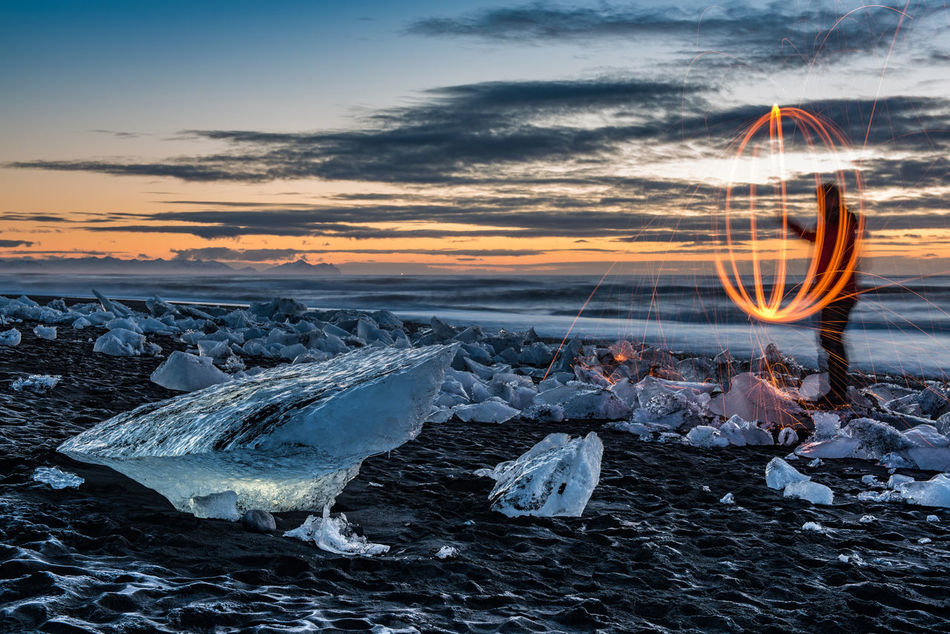 """Fire, ice and diamonds. Some of the chunks of ice, some big, some smaller, floating into the ocean from Jökulsárlón glacier lagoon, wash back up onto Diamond Beach. Here I greeted the sunrise with fire and steel. (Nikon D810 24-70mm f/2.8 ƒ/11 48mm 2.5"""" iso 31) Beach Cold Dawn Fire Glacier Glacier Lagoon Ice Iceland Jökulsárlón Landscape Long Exposure Outdoors Scandinavia Sea Sunrise Unrecognizable Person Volcanic Landscape Water Winter"""