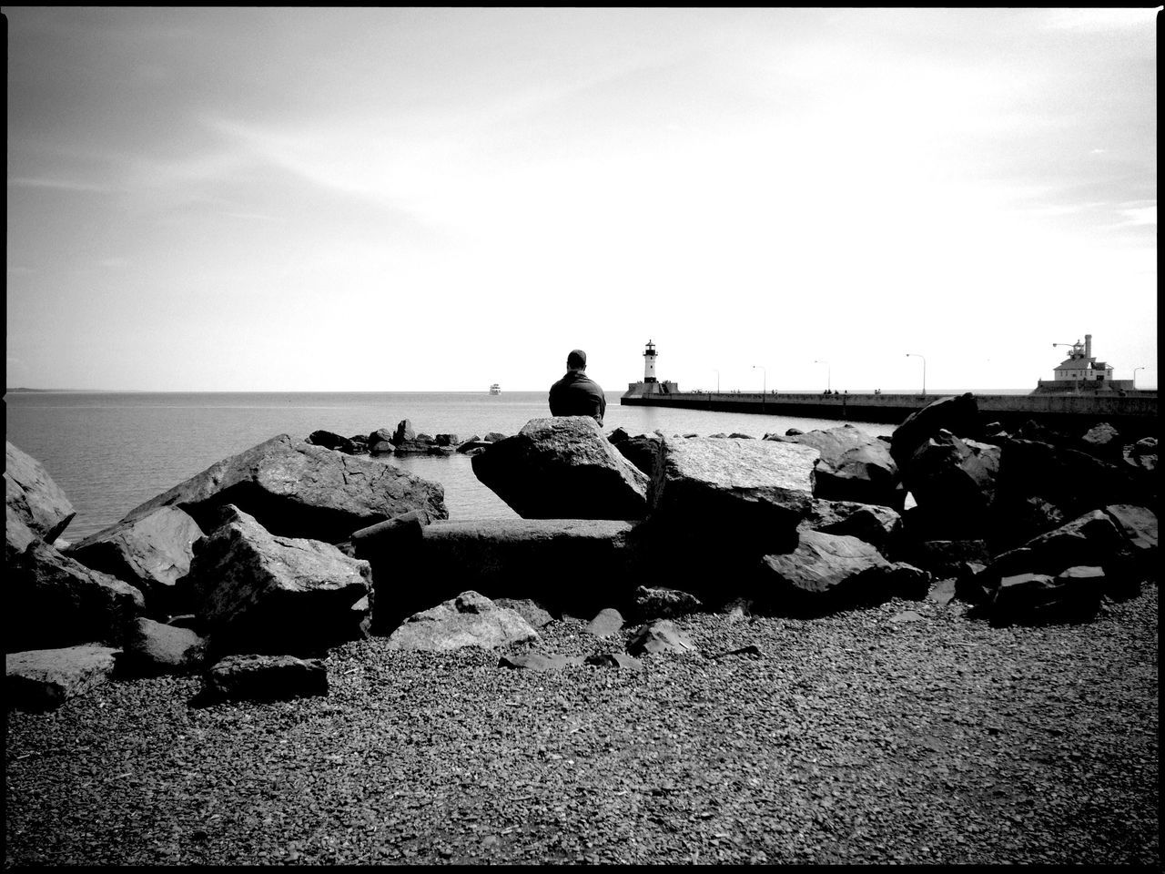 Rear View Of Man By Rocks At Sea Shore Against Sky