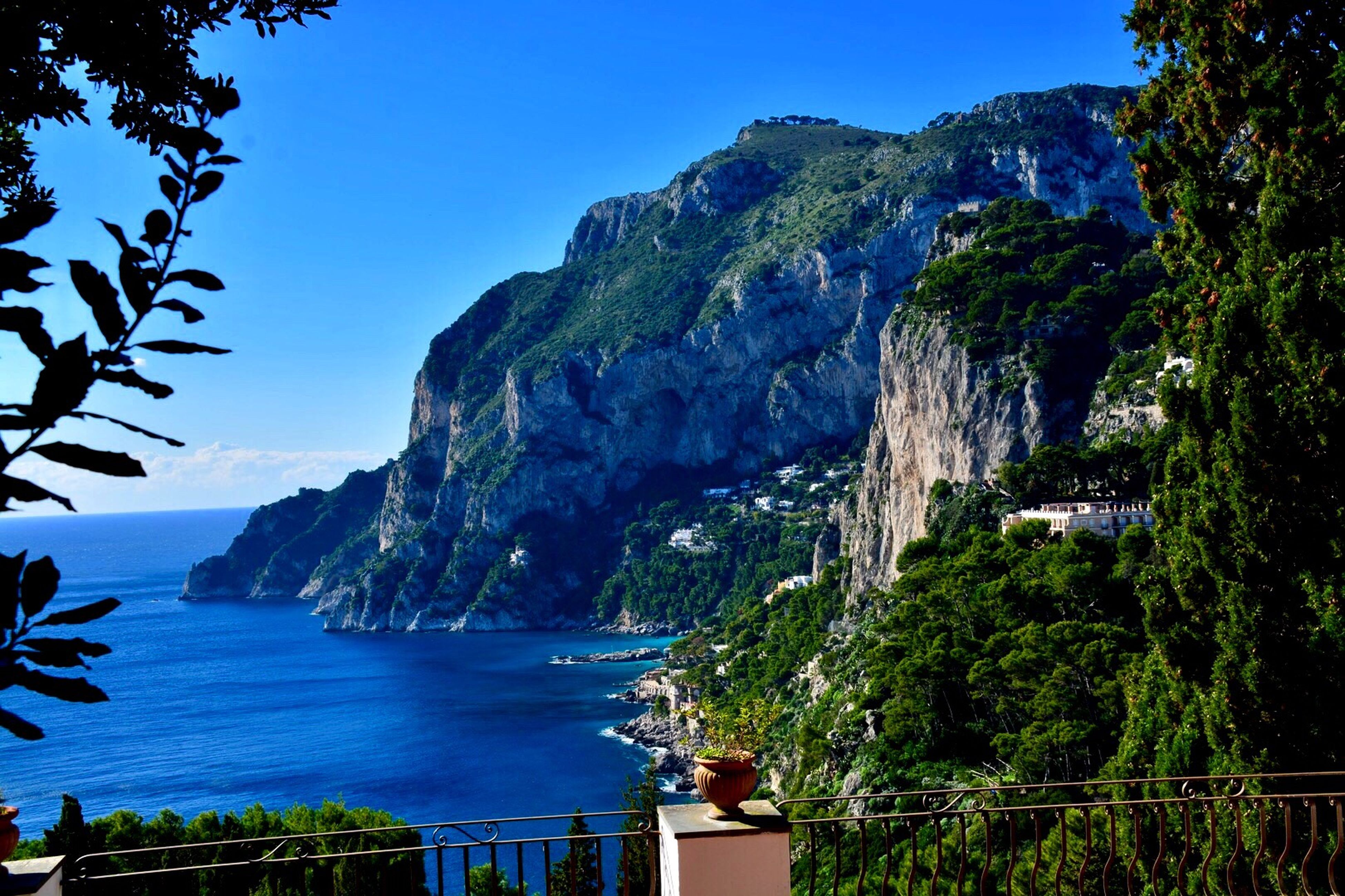 sea, water, mountain, scenics, beauty in nature, rock - object, nature, cliff, blue, steep, tree, tranquil scene, outdoors, beach, travel destinations, vacations, no people, horizon over water, landscape, nautical vessel, sky, architecture, day, yacht