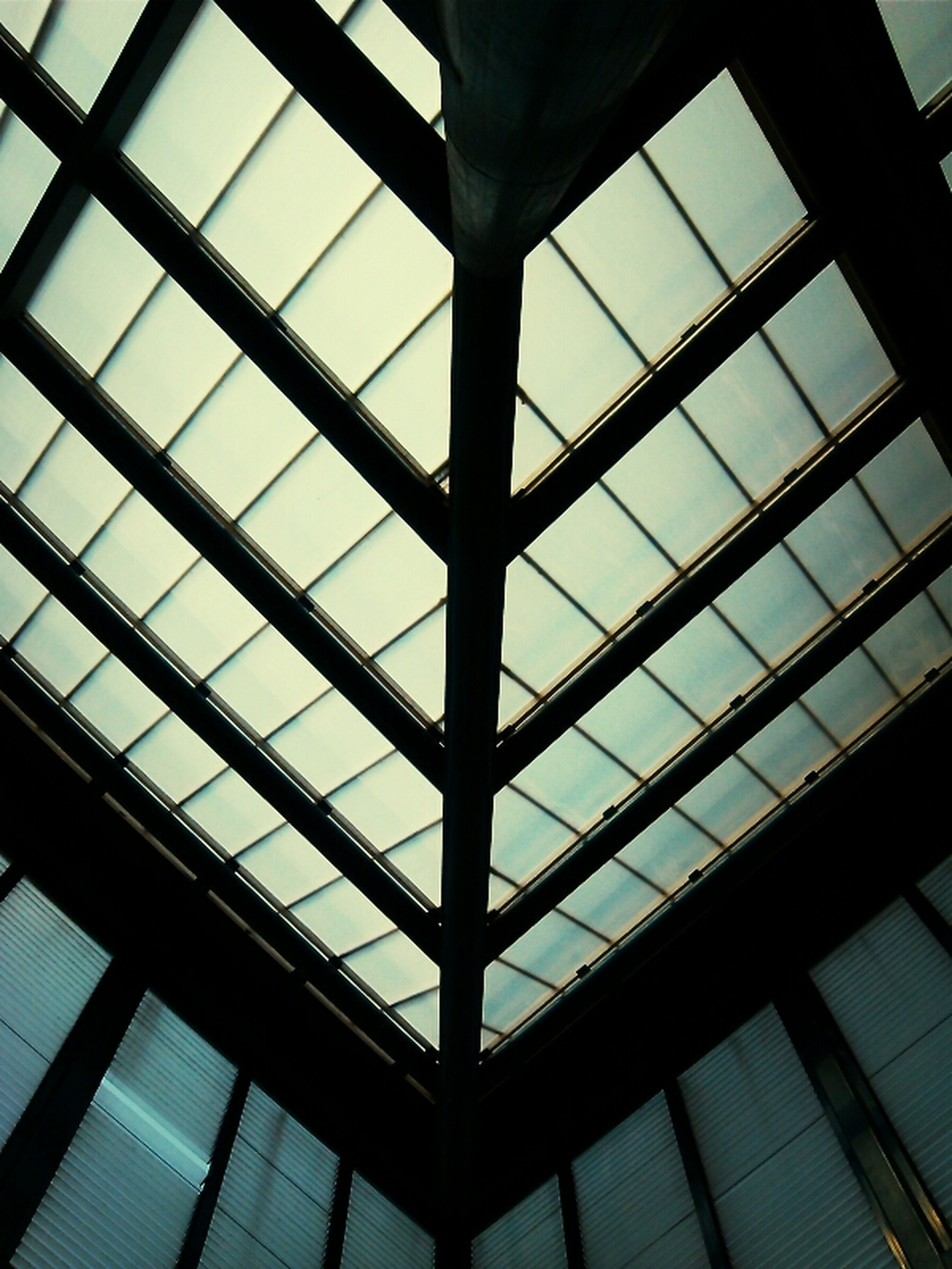 indoors, glass - material, window, architecture, built structure, low angle view, transparent, ceiling, modern, full frame, glass, skylight, pattern, backgrounds, architectural feature, building, reflection, geometric shape, sky, building exterior