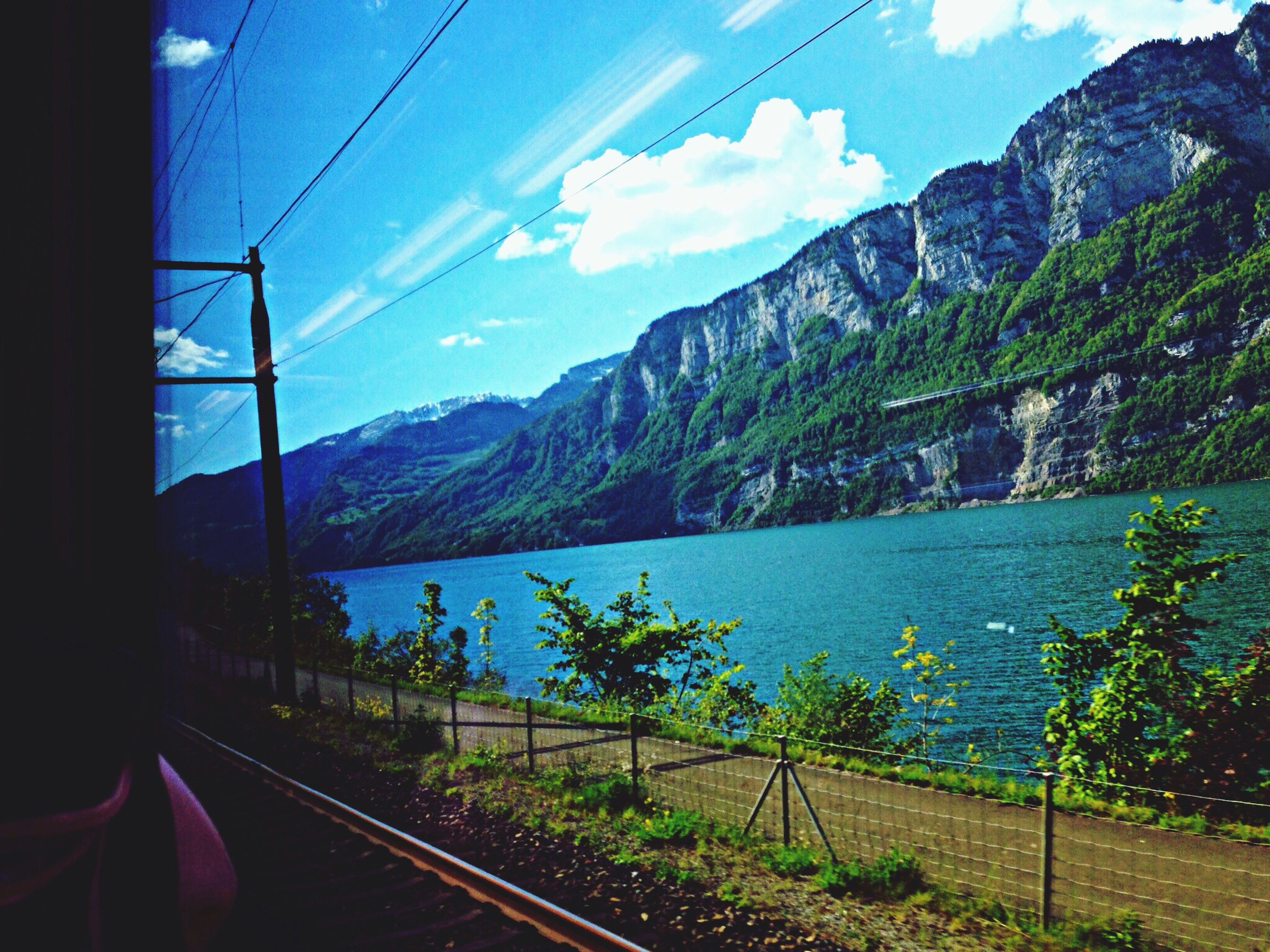 mountain, power line, sky, transportation, mountain range, railroad track, tranquility, tranquil scene, connection, electricity pylon, cable, scenics, landscape, nature, beauty in nature, water, rail transportation, electricity, blue, power supply