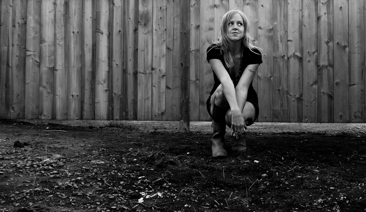 Black And White Blond Hair Dirt Fence Full Length Nature One Person Outdoors Portrait Real People Rubber Boots Sitting Woman