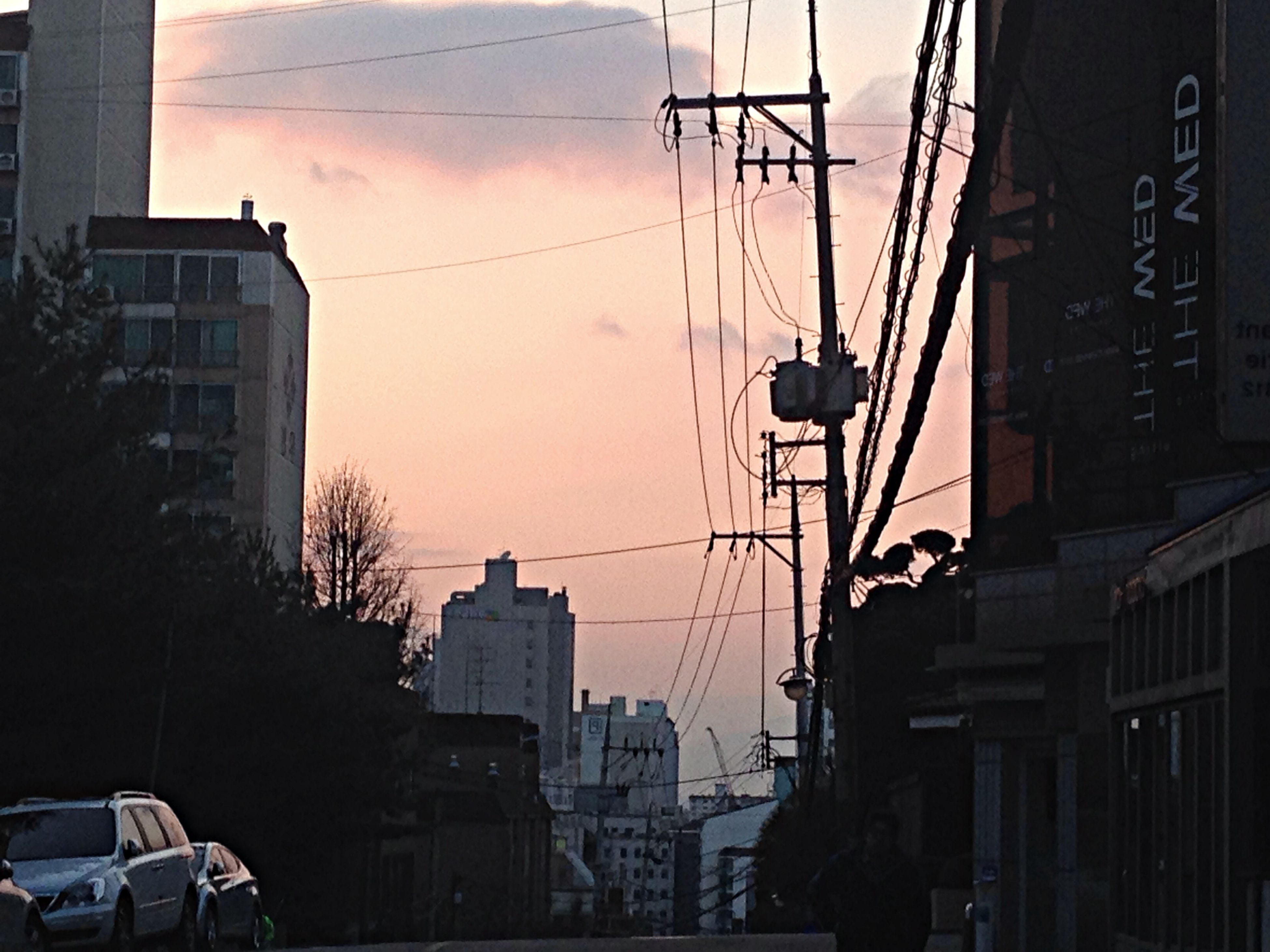 building exterior, architecture, built structure, city, transportation, power line, car, mode of transport, land vehicle, street, sky, electricity pylon, cable, building, city life, sunset, residential building, residential structure, city street, street light
