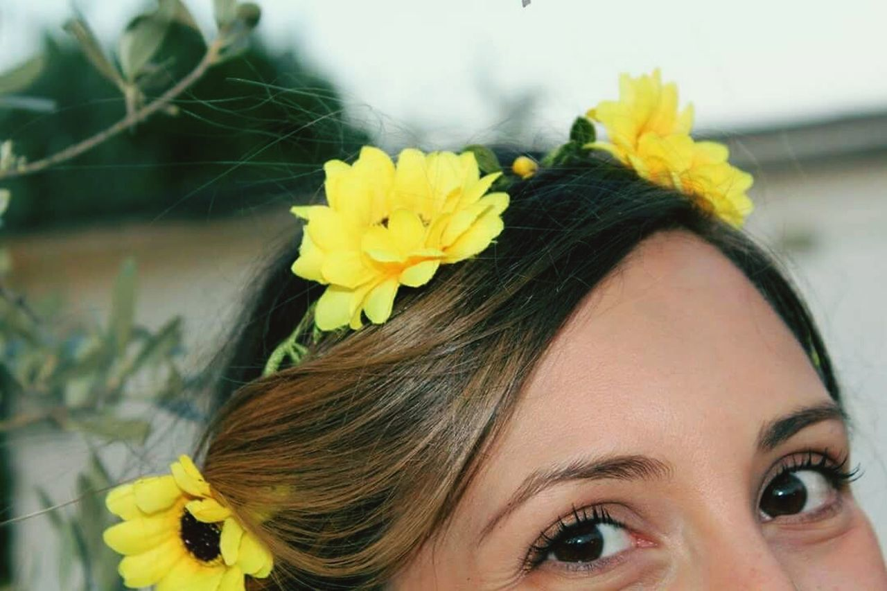 flower, one person, yellow, young adult, wearing flowers, real people, young women, portrait, focus on foreground, close-up, beautiful woman, day, headshot, front view, looking at camera, outdoors, lifestyles, fragility, human face, happiness, women, smiling, freshness, bride, nature, flower head, adults only, adult, people