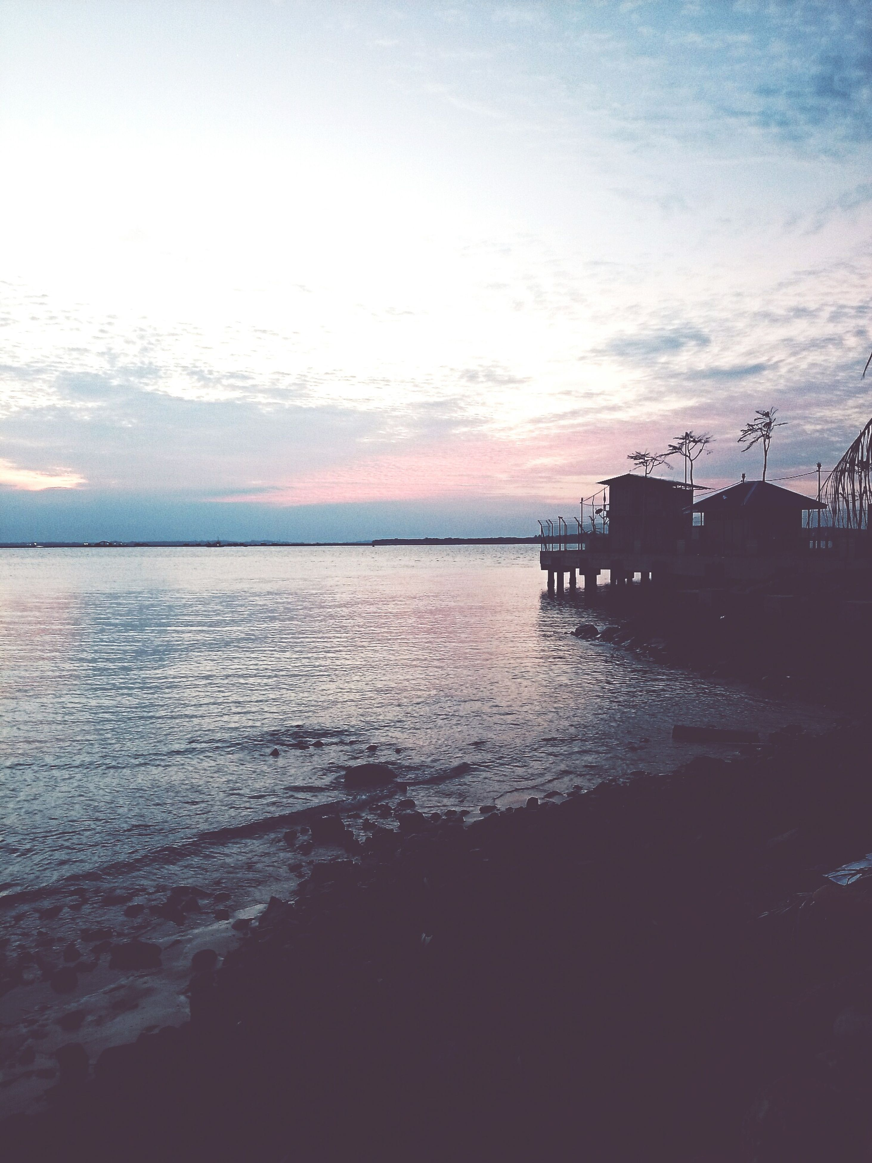 sea, water, horizon over water, sky, tranquil scene, scenics, tranquility, beauty in nature, sunset, beach, nature, pier, idyllic, shore, cloud - sky, built structure, silhouette, outdoors, calm, incidental people