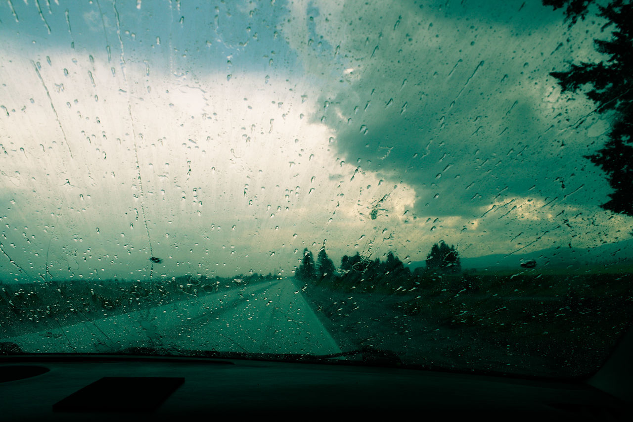 glass - material, transparent, vehicle interior, car, car interior, windshield, wet, window, rain, drop, weather, land vehicle, water, raindrop, rainy season, transportation, glass, mode of transport, no people, car point of view, indoors, sky, looking through window, windscreen, cloud - sky, nature, condensation, road, day, close-up