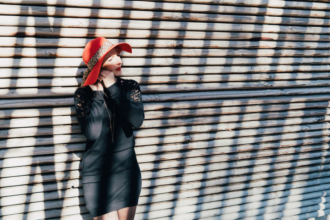 Adult Black Dress Light Light And Shadow Lines Lines And Shapes One Person One Woman Only One Young Woman Only Outdoors People Real People Red Red Hat Standing Wall Wall - Building Feature Women Young Adult