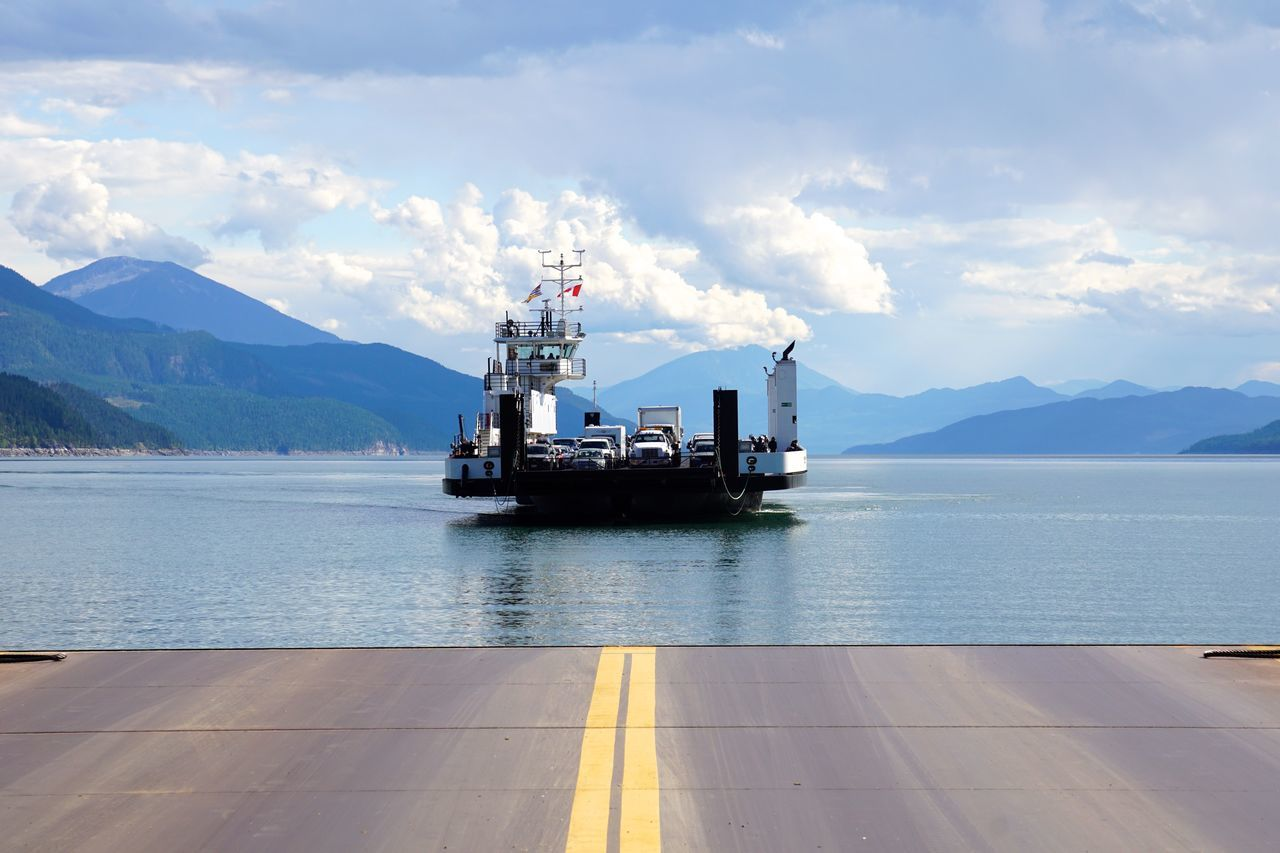 Ferry arriving at the end of the road Cars Crossing Day End Of The Road Ferry Fossil Fuel Gas Harbor Mountain Nautical Vessel No People Offshore Outdoors Sky Transportaion Trucks Vehicles Water