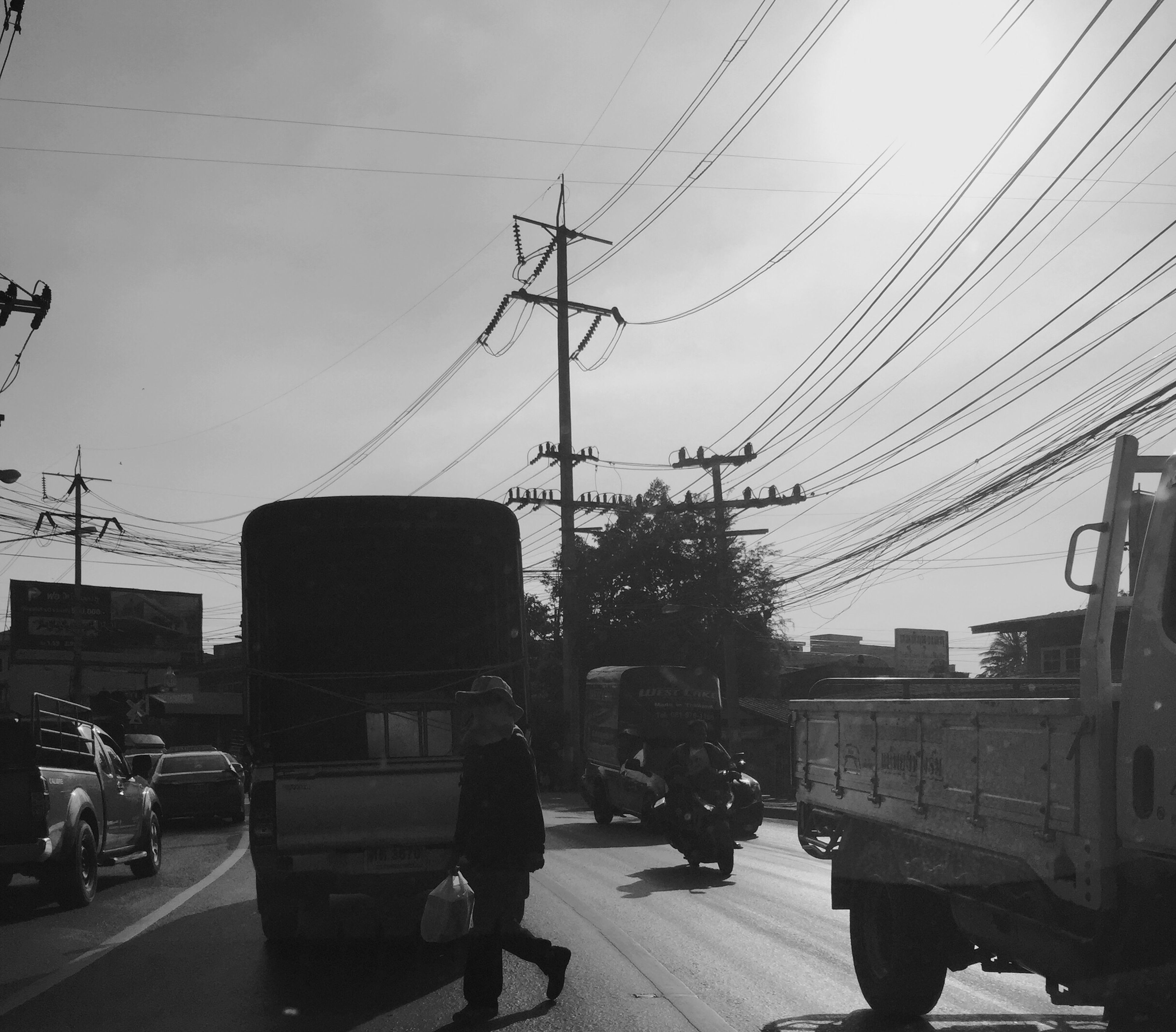 transportation, land vehicle, car, mode of transport, street, power line, cable, built structure, building exterior, city, sky, architecture, outdoors, electricity, electricity pylon, day, city life, road, connection, no people