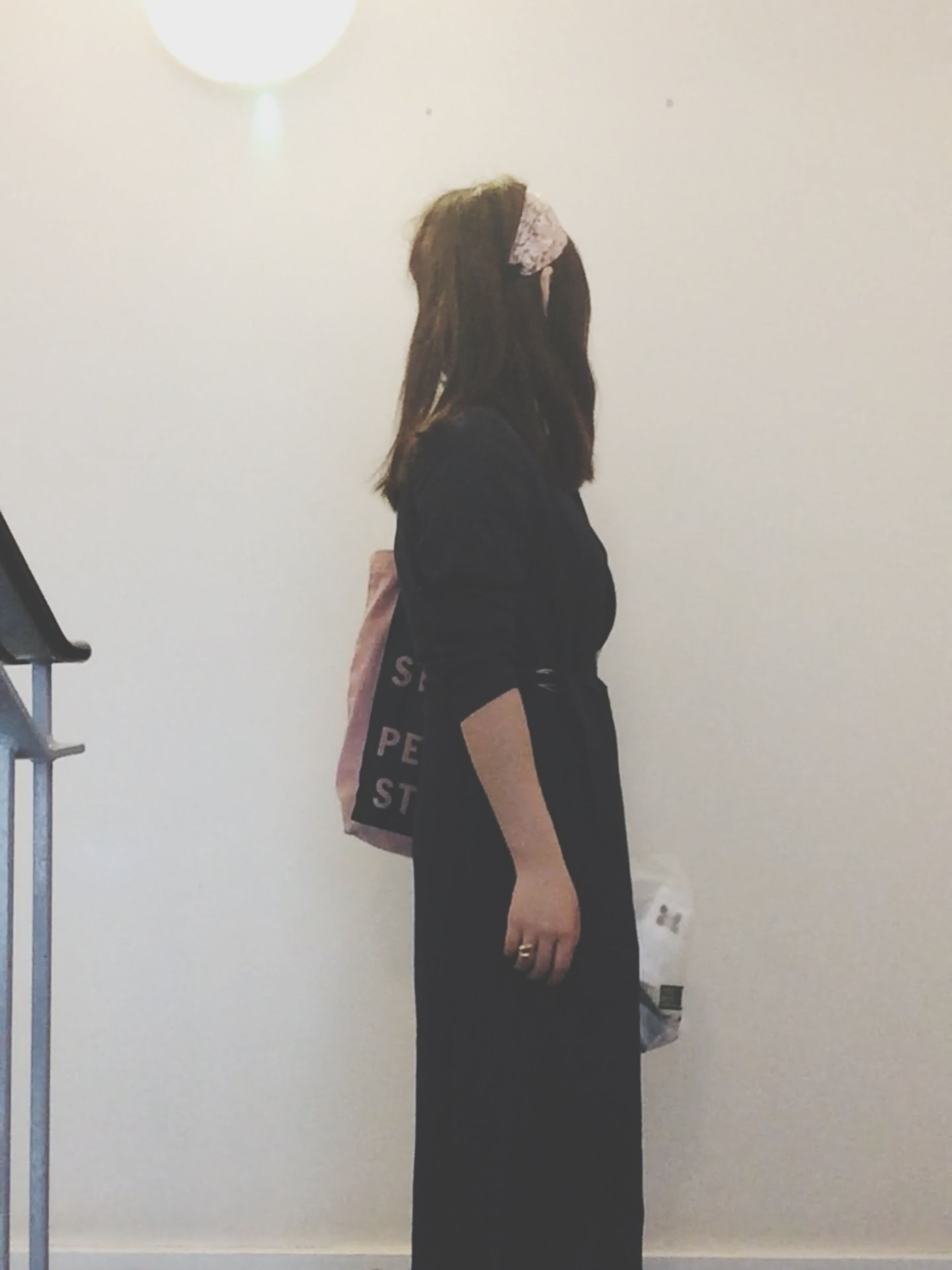 indoors, standing, lifestyles, wall - building feature, young adult, three quarter length, leisure activity, waist up, young women, casual clothing, front view, person, wall, long hair, home interior, obscured face, architecture, rear view