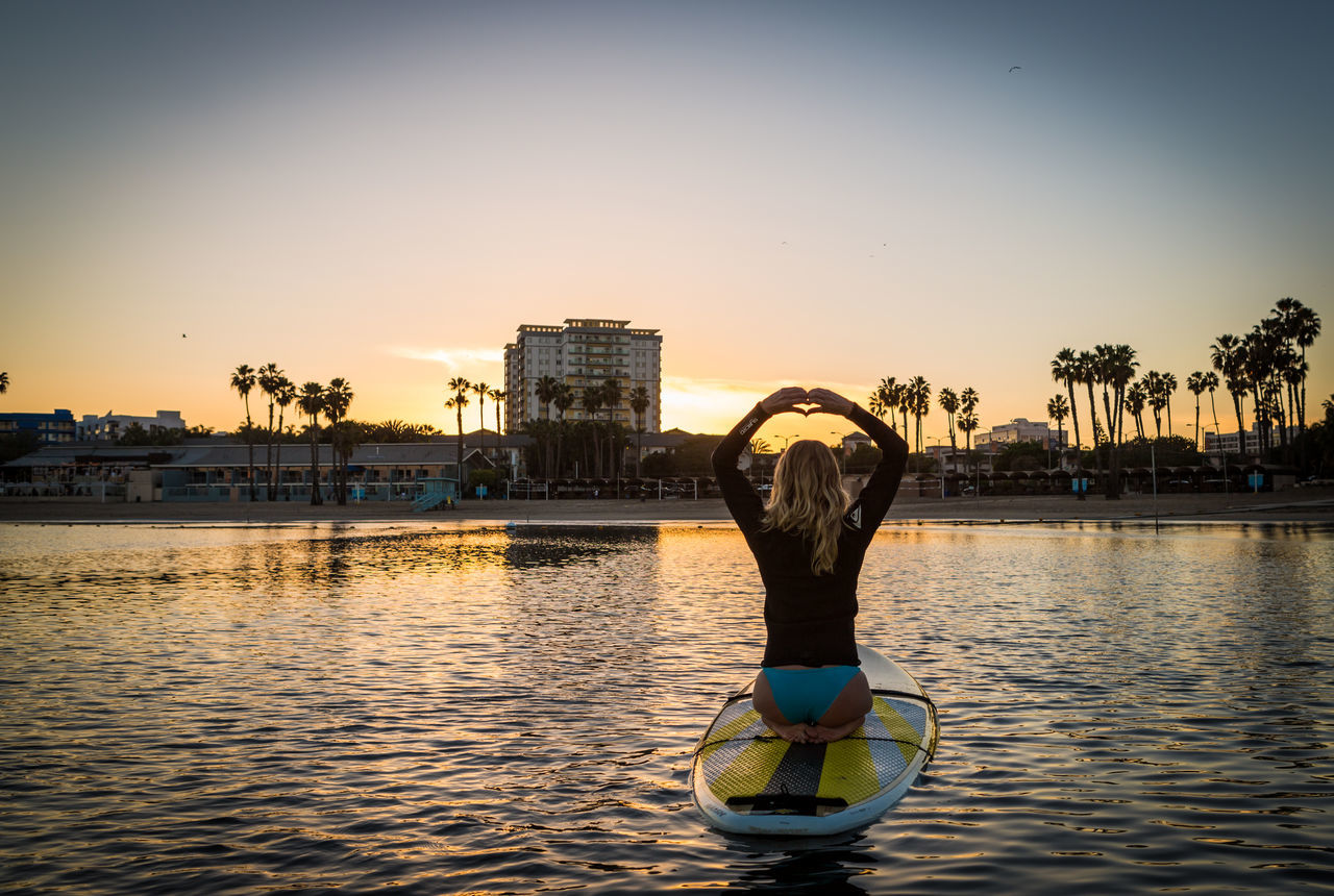 water, sunset, real people, leisure activity, rear view, built structure, lifestyles, clear sky, architecture, outdoors, sky, river, one person, nautical vessel, tree, building exterior, women, nature, day, people