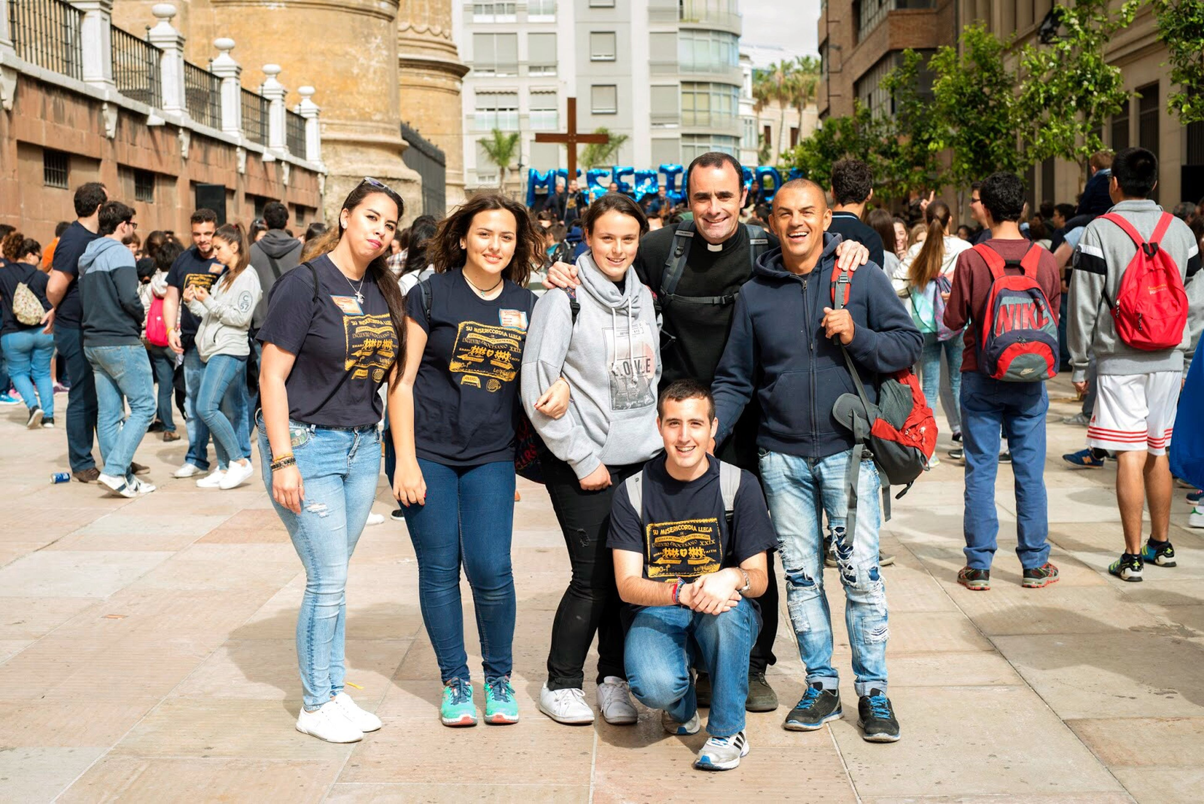 lifestyles, casual clothing, leisure activity, togetherness, person, large group of people, building exterior, standing, full length, architecture, men, built structure, friendship, young women, street, young adult, front view, city life, city