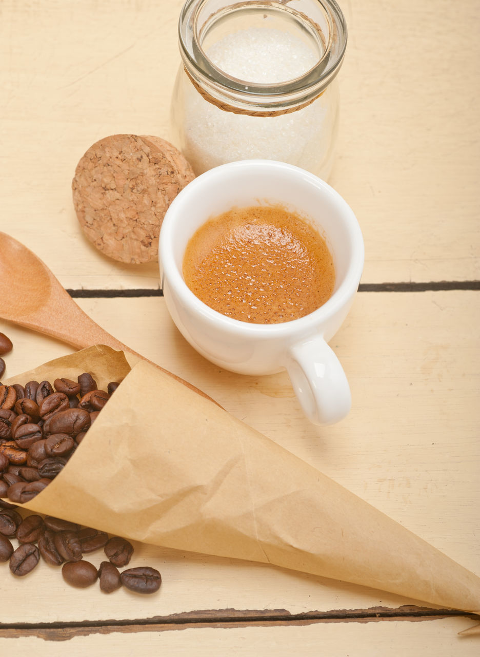High Angle View Of Roasted Coffee Beans By Cup And Sugar On Table
