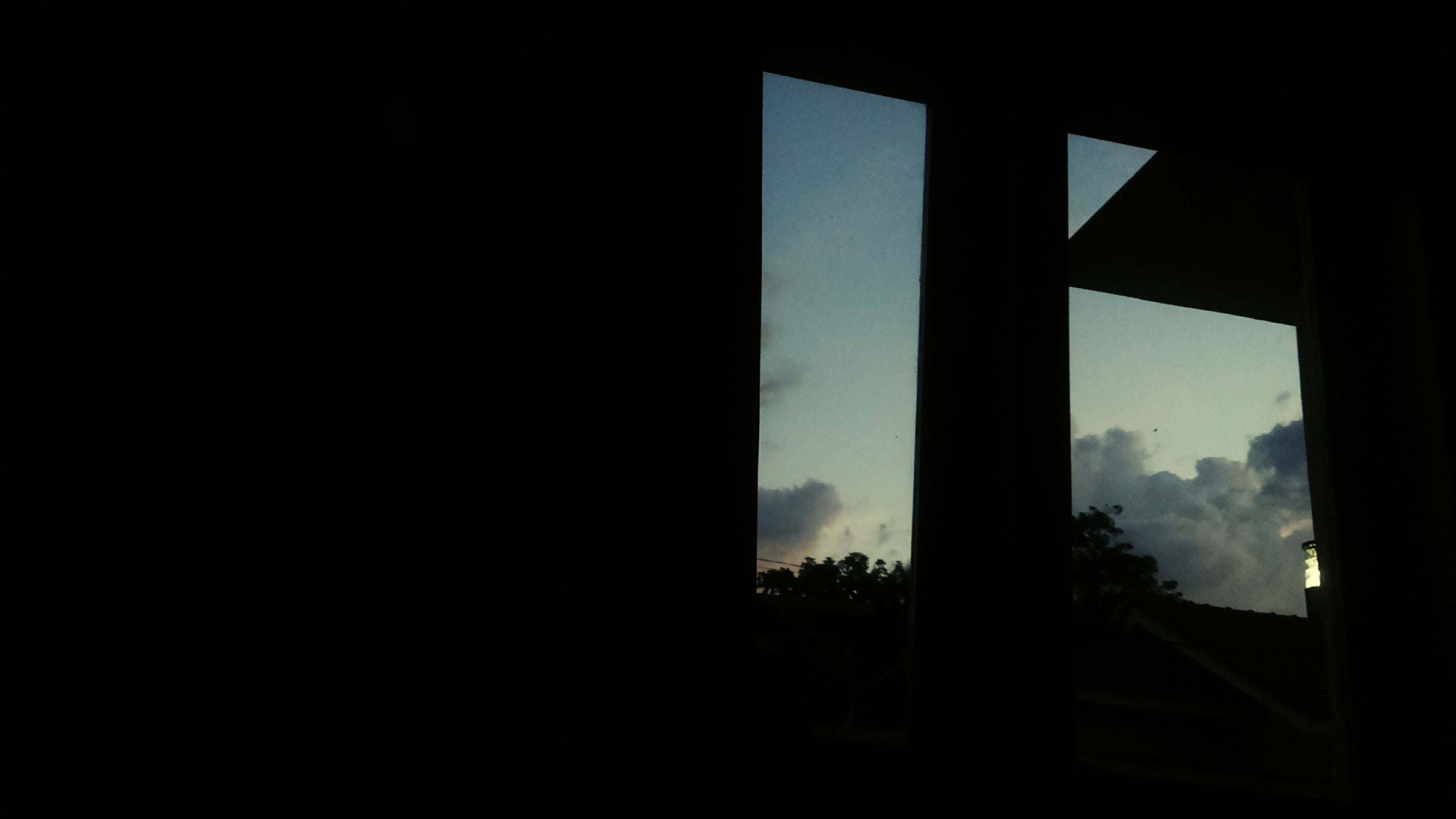 indoors, window, silhouette, dark, built structure, architecture, copy space, sky, tree, glass - material, transparent, house, day, looking through window, no people, home interior, sunlight, nature, clear sky, curtain