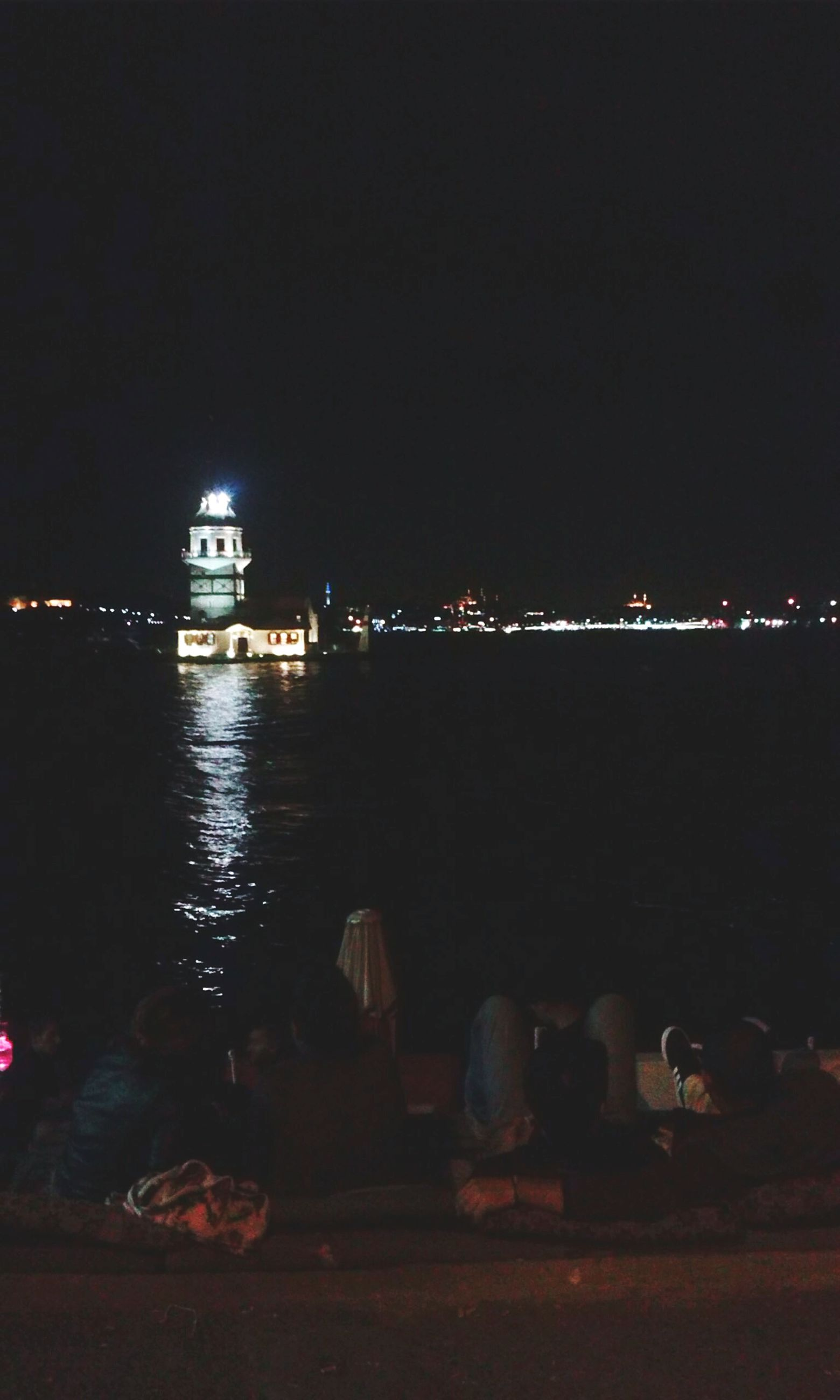 night, illuminated, water, copy space, sea, built structure, dark, building exterior, architecture, men, sky, lifestyles, clear sky, city, leisure activity, outdoors, river, reflection, lighting equipment